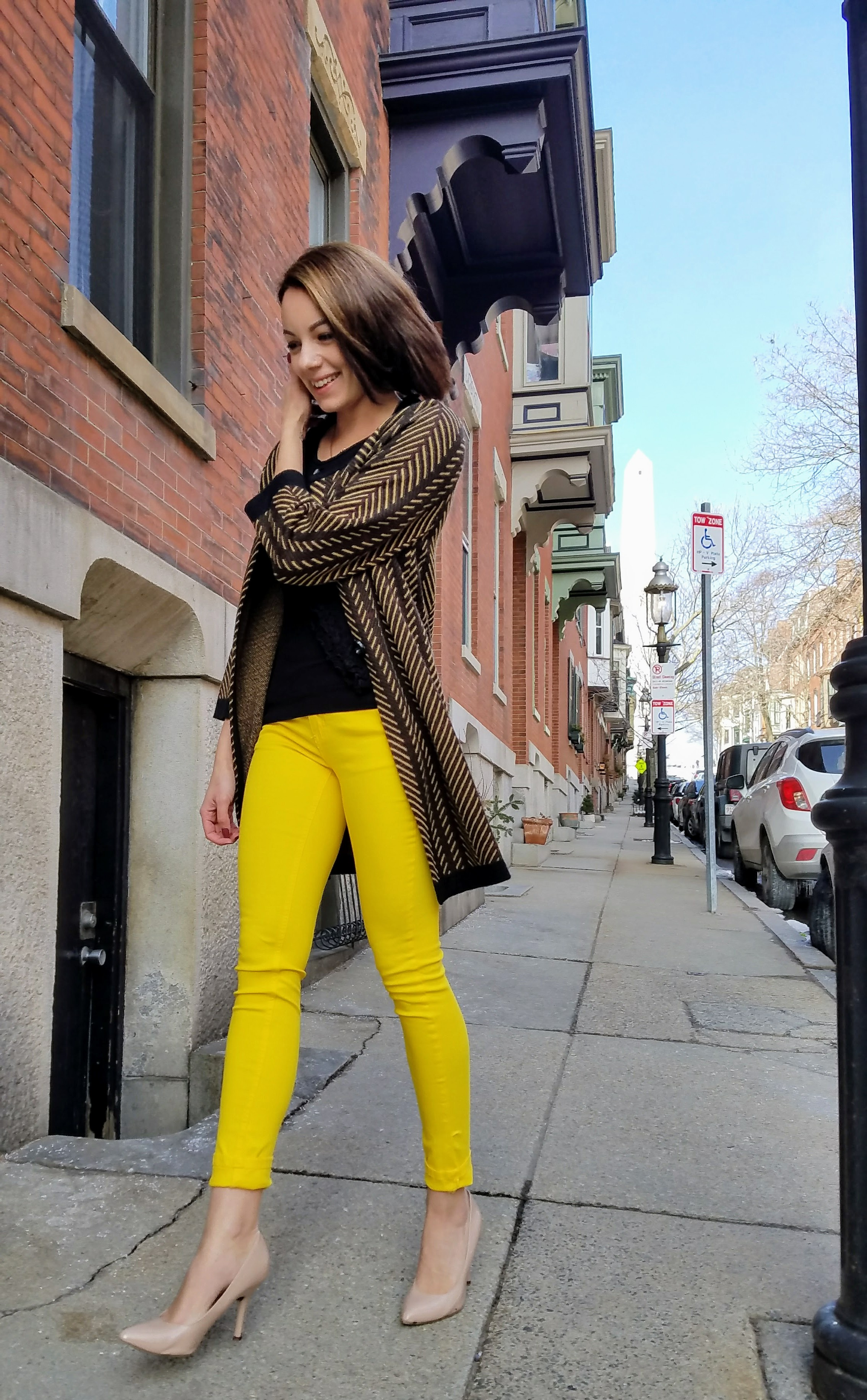 A girl walking in Boston wearing yellow pants, nude heels, and a cardigan for her blog.