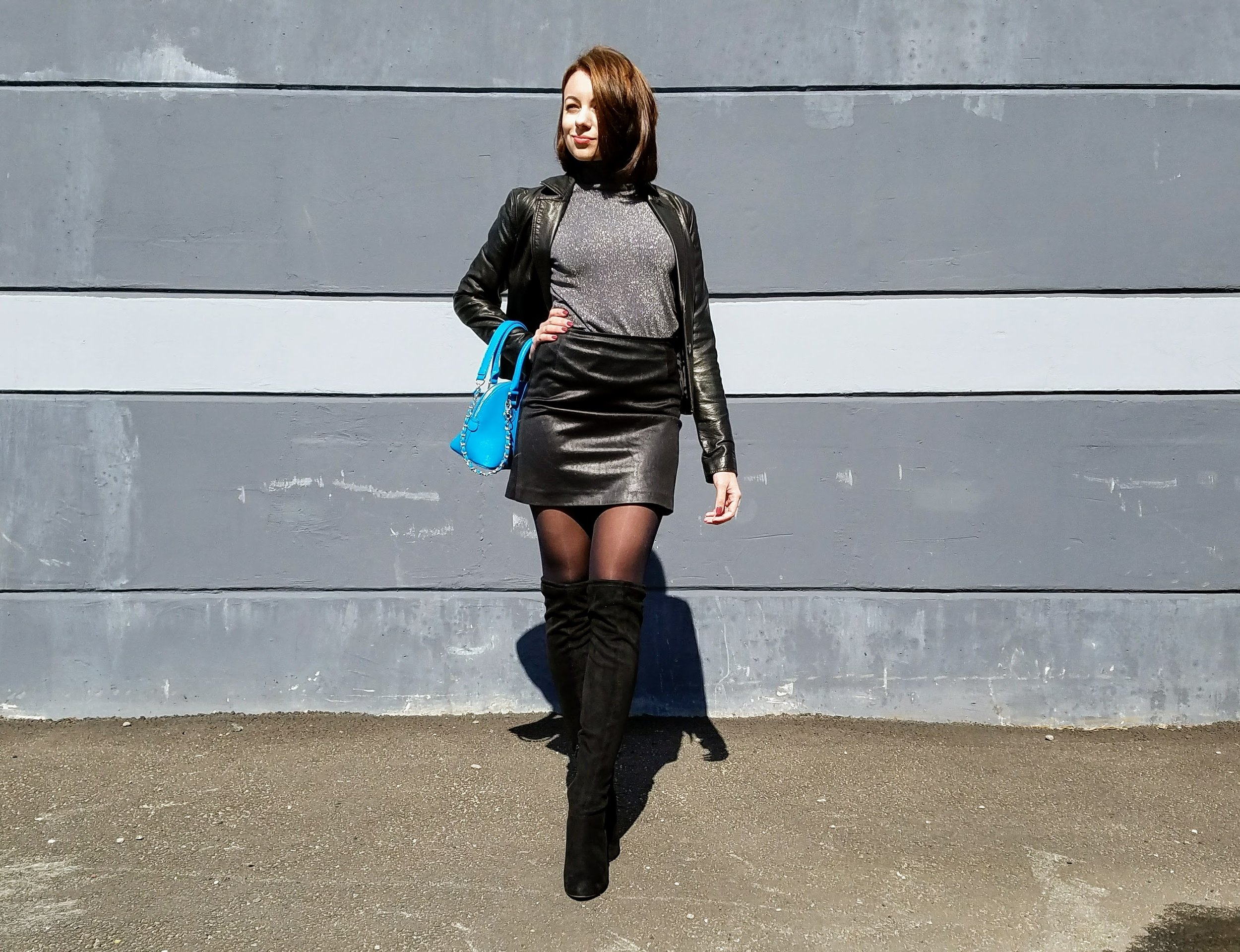 Black leather skirt and jacket, black thigh high boots, blue bag, gray turtleneck.