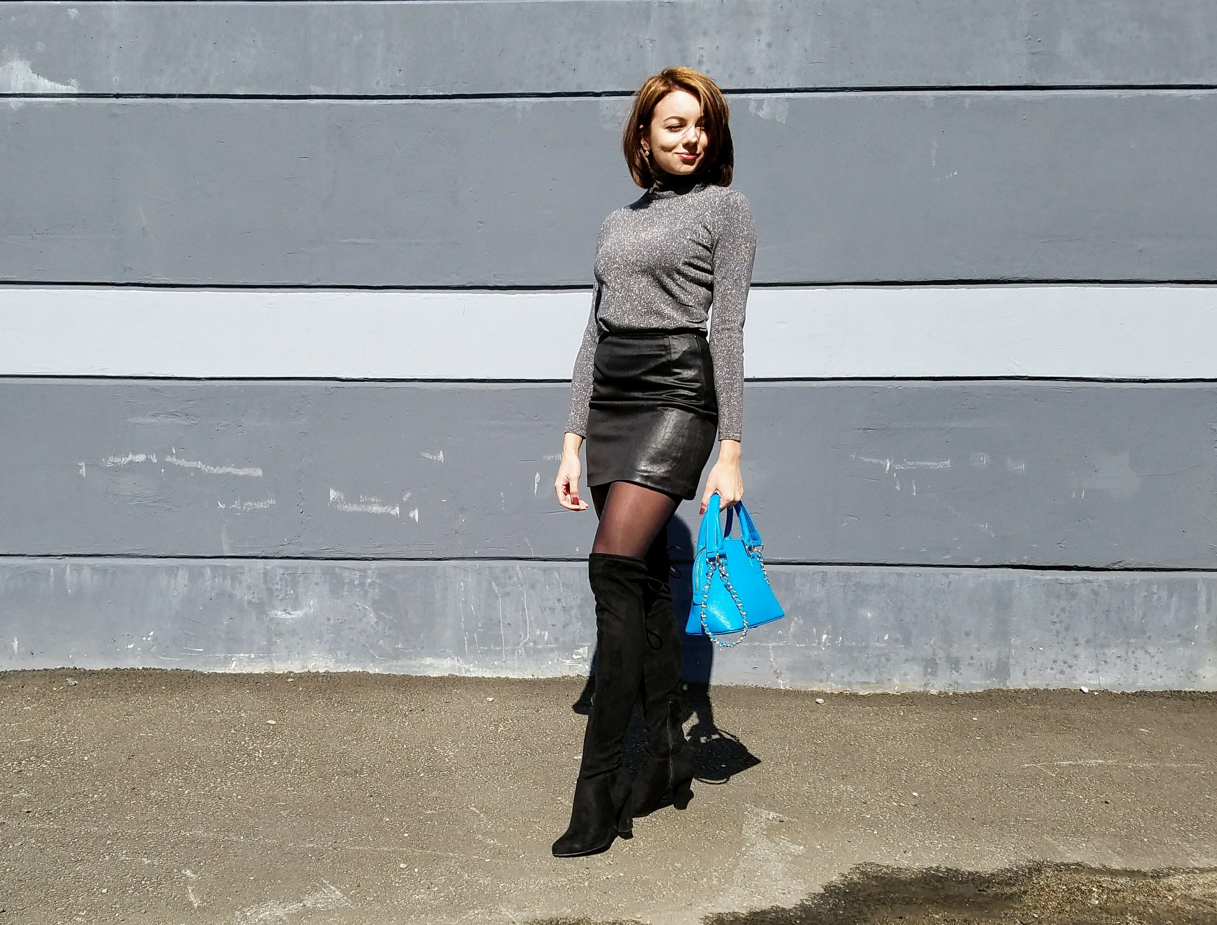 Gray turtleneck, black leather skirt, black thigh high boots, blue purse.