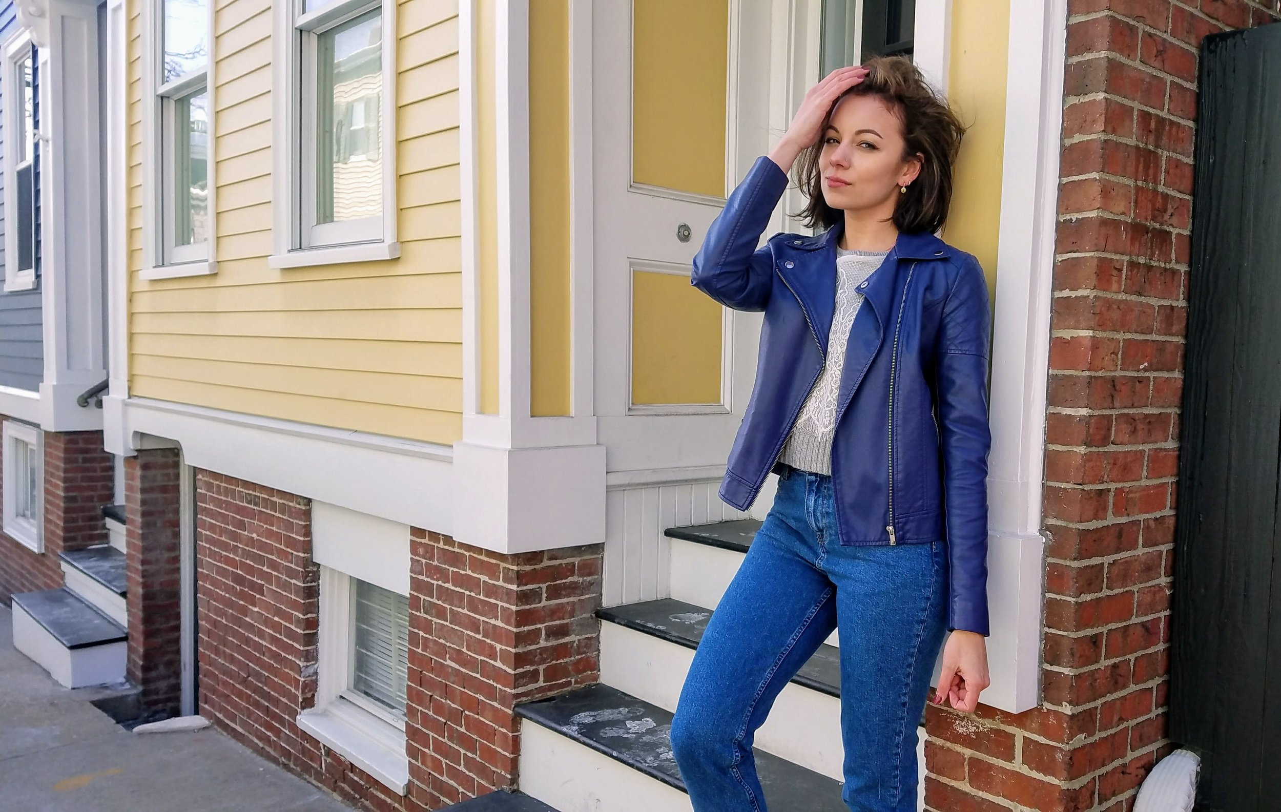 Blue jacket, gray sweater, mom jeans, Nike sneakers outfit leaning on brick building
