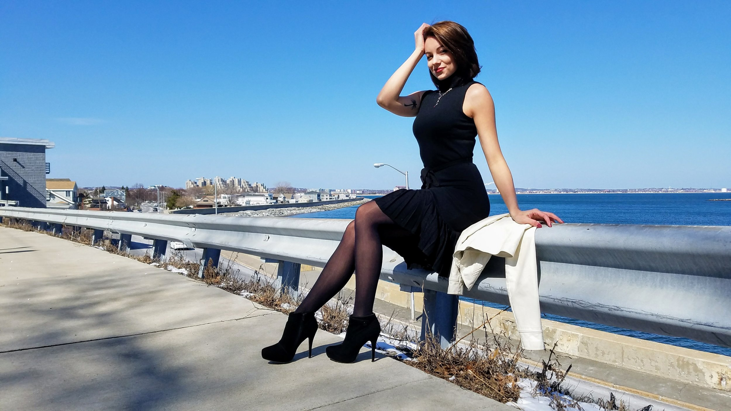 A girl wearing a black dress and black ankle boots near the beach.