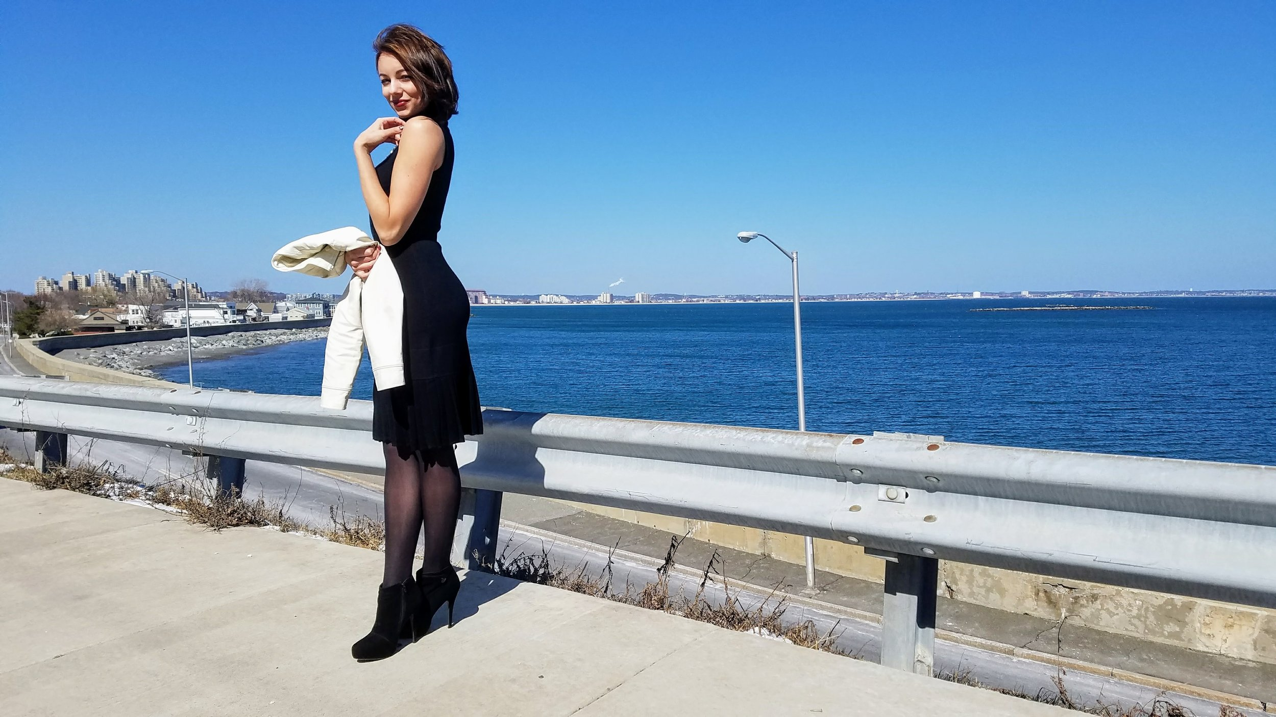 Beach view with a girl wearing a black turtleneck dress, black ankle boots, and holding a white leather jacket.