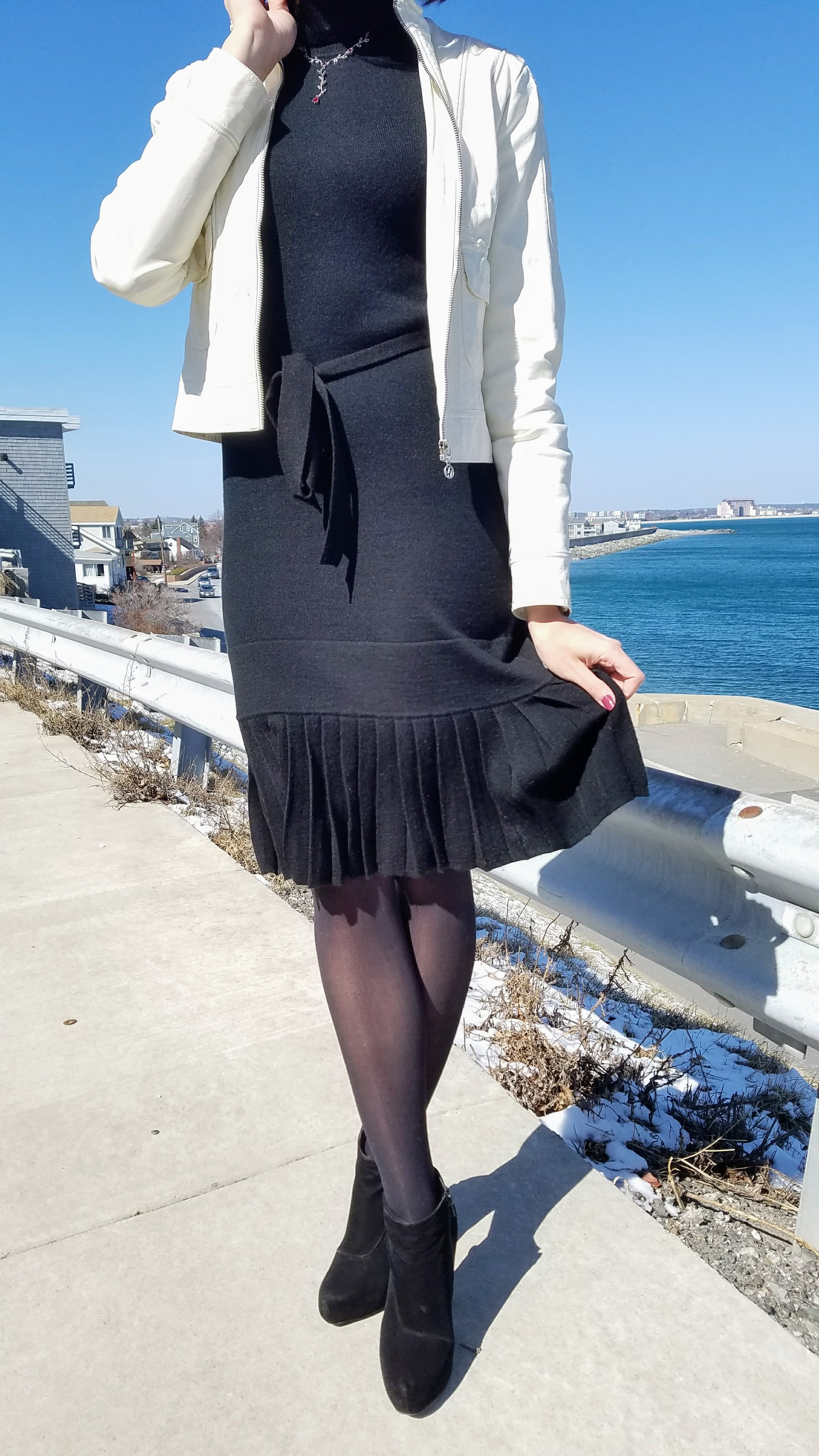An outfit closeup. A black turtleneck dress, black tights, black ankle boots, and a white leather jacket.