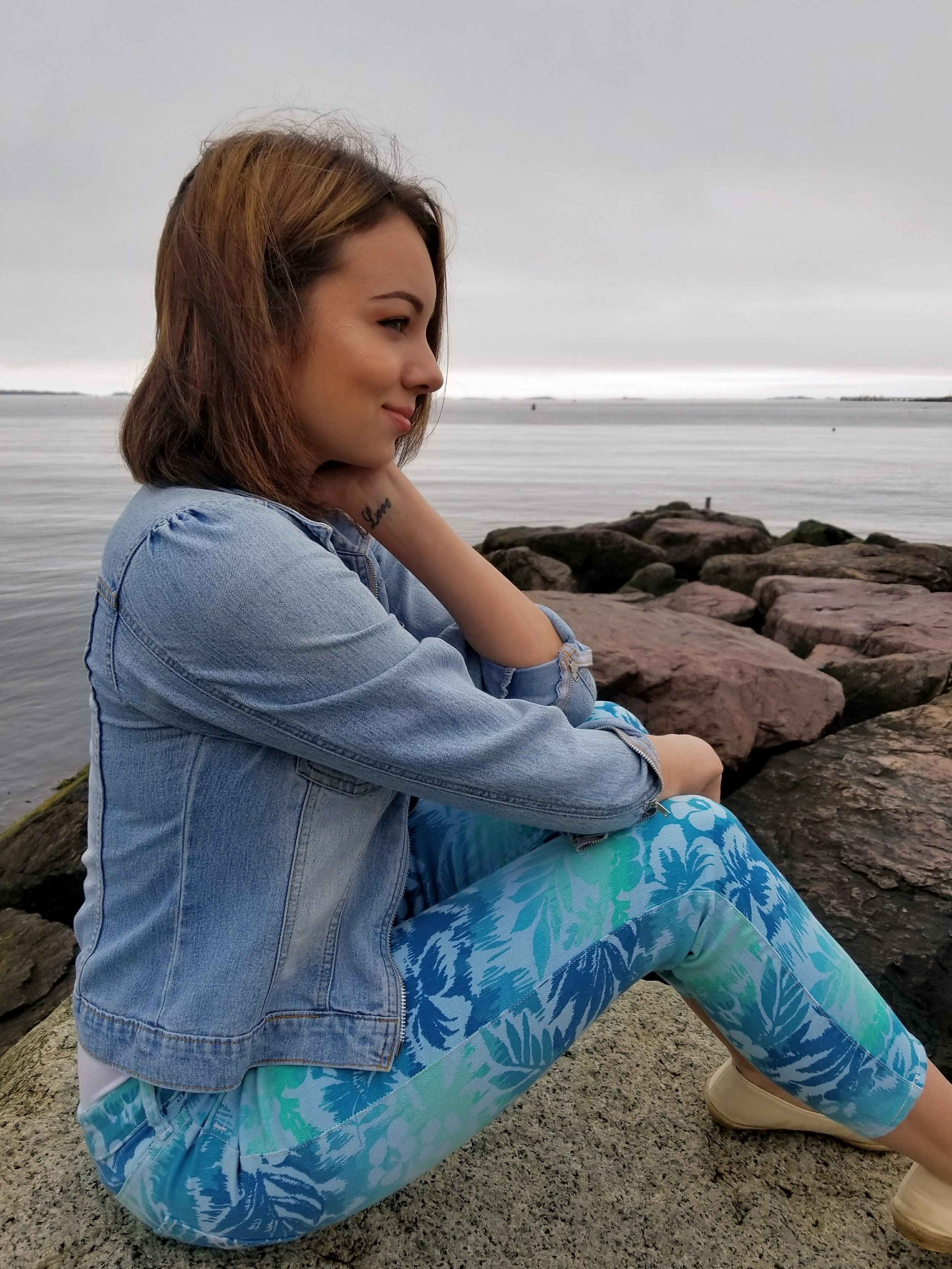 A girl sitting on the rocks by the beach, wearing pants with blue and green pattern and jean jacket.