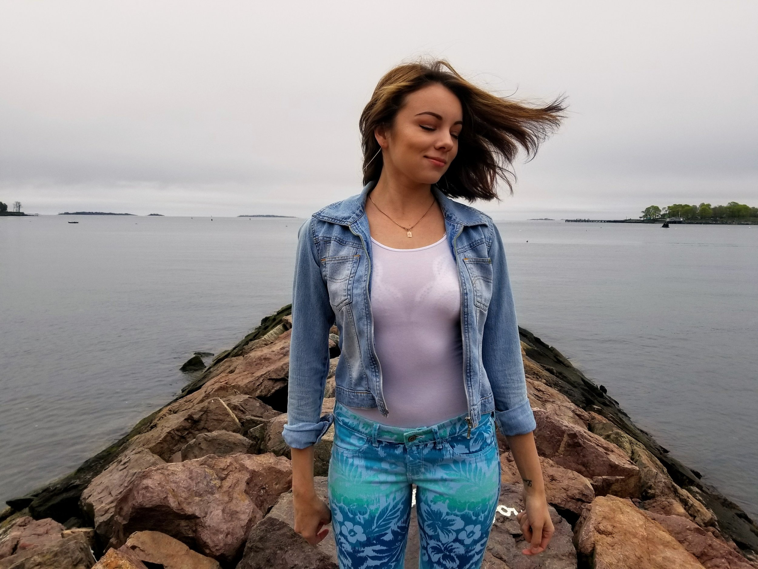 A blogger standing on the rocks by the beach flipping her hair.