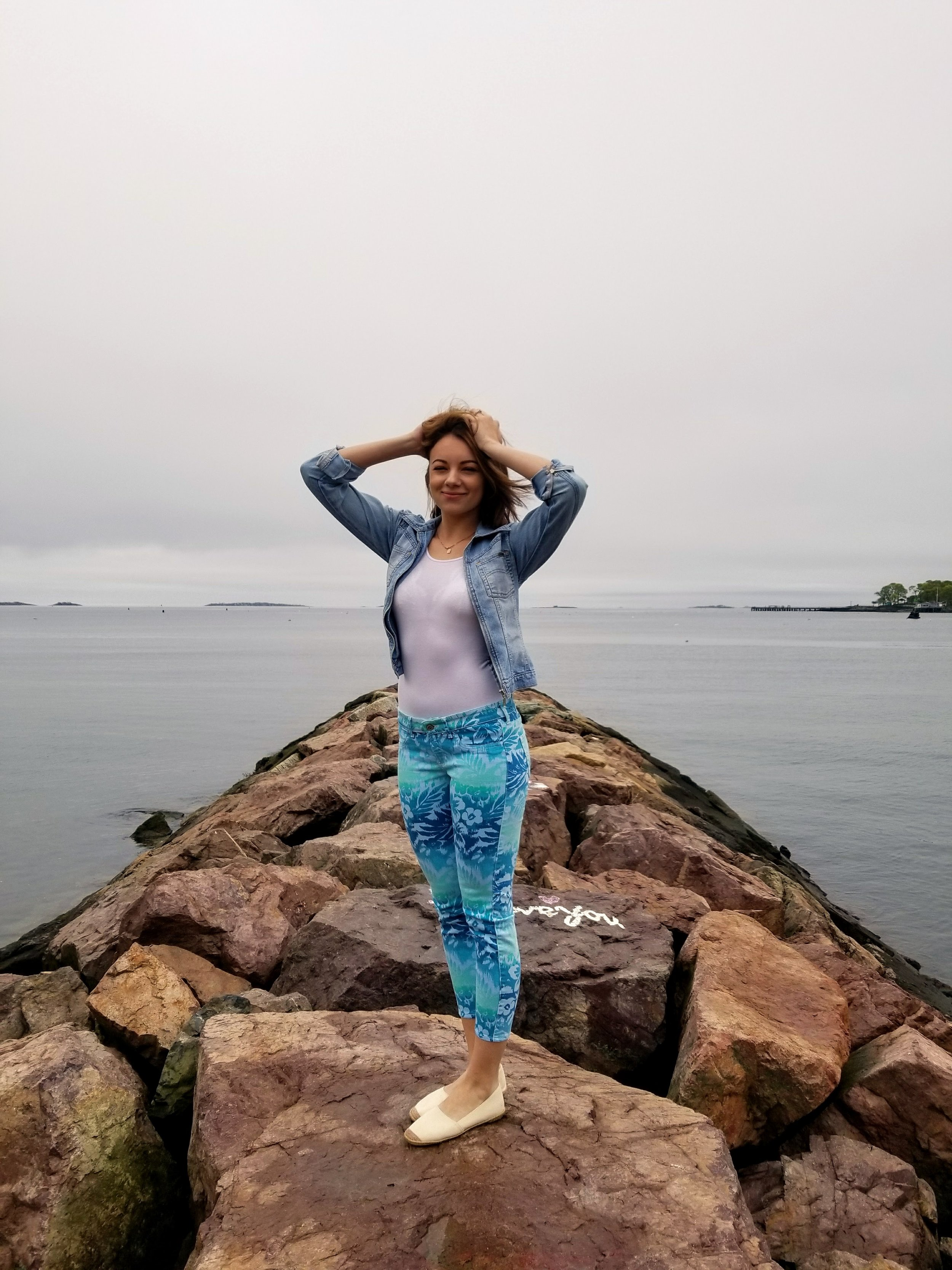 A blogger posing by the beach, wearing colorful pants with blue and green pattern, white t-shirt, jean jacket.