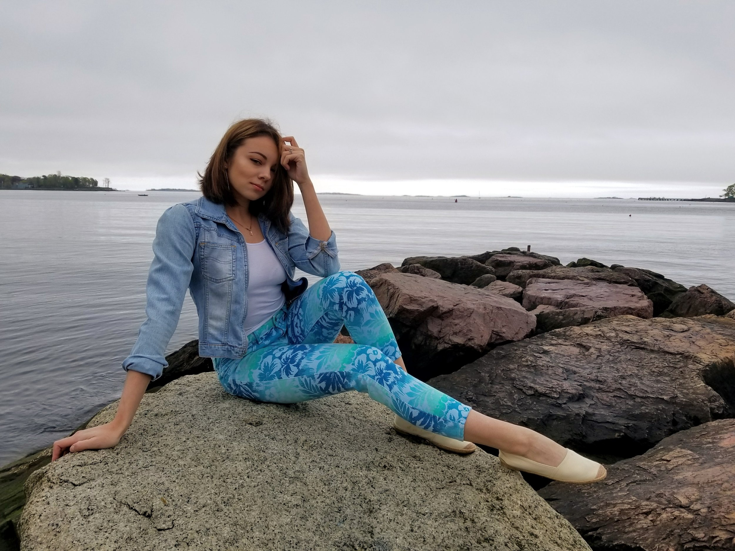 A blogger sitting on a big rock at the beach.