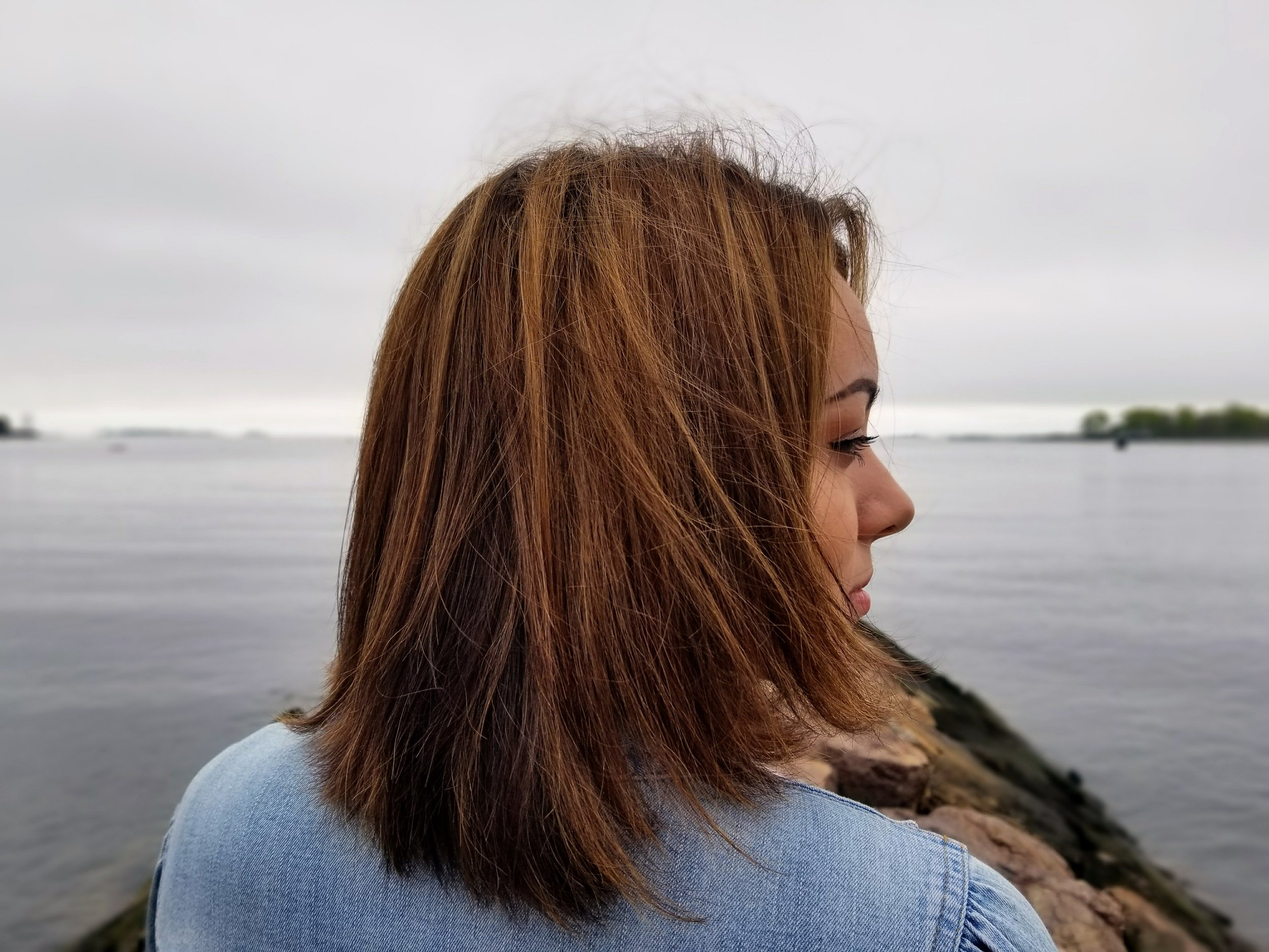 A close up of a girl looking to the side with the beach in front of her.