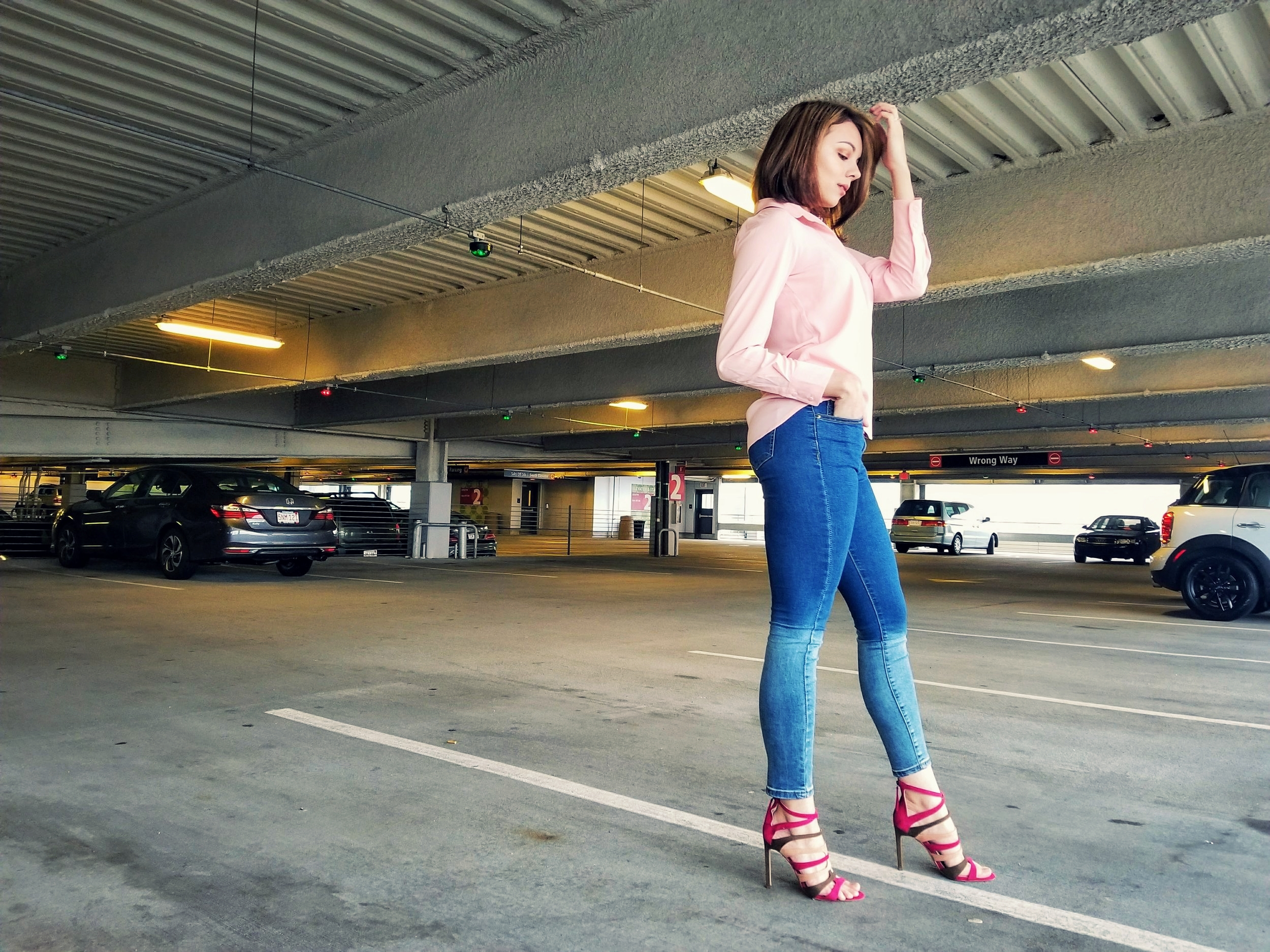 A blogger posing and wearing a pink blouse, cut off pants, and lace up heels.