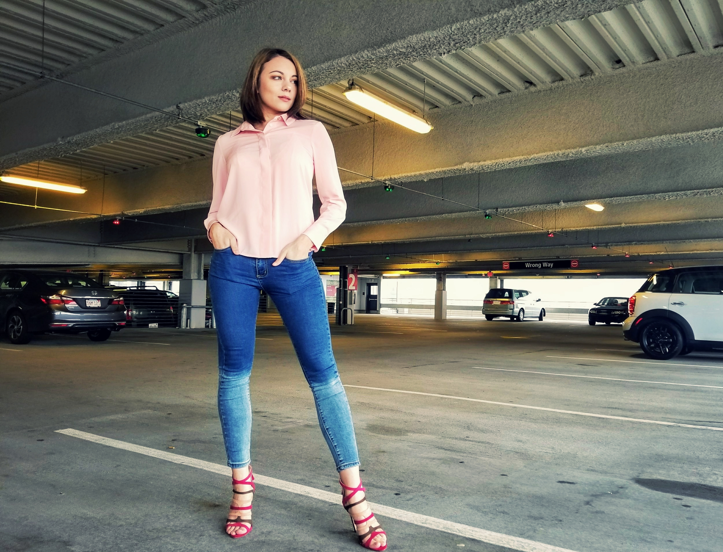 A blogger posing, looking to the side, wearing a pink long-sleeve blouse, washed out jeans, and lace up heels.