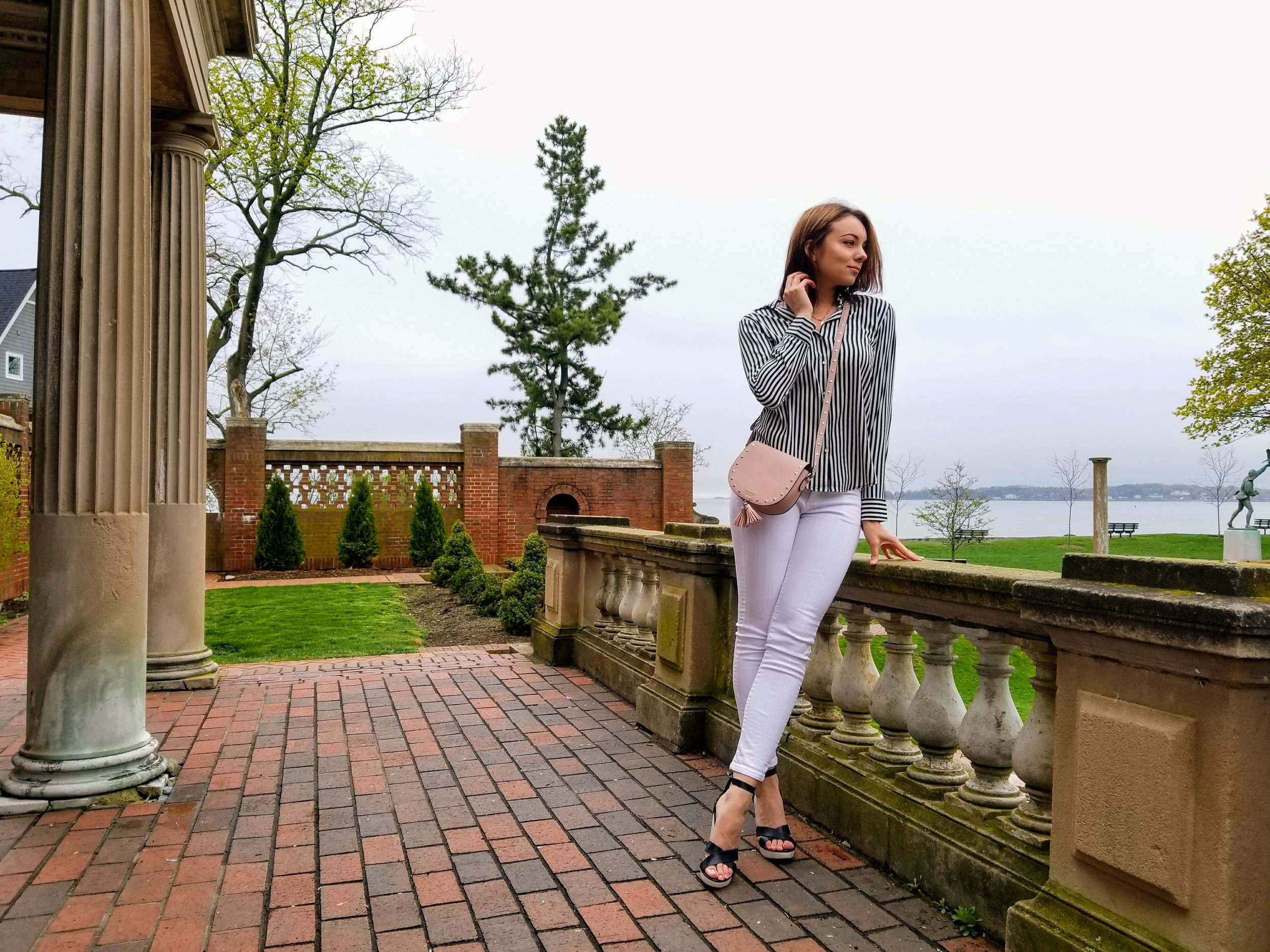 A blogger posing in the garden, wearing white jeans, black wedges, black and white blouse, and pink bag.