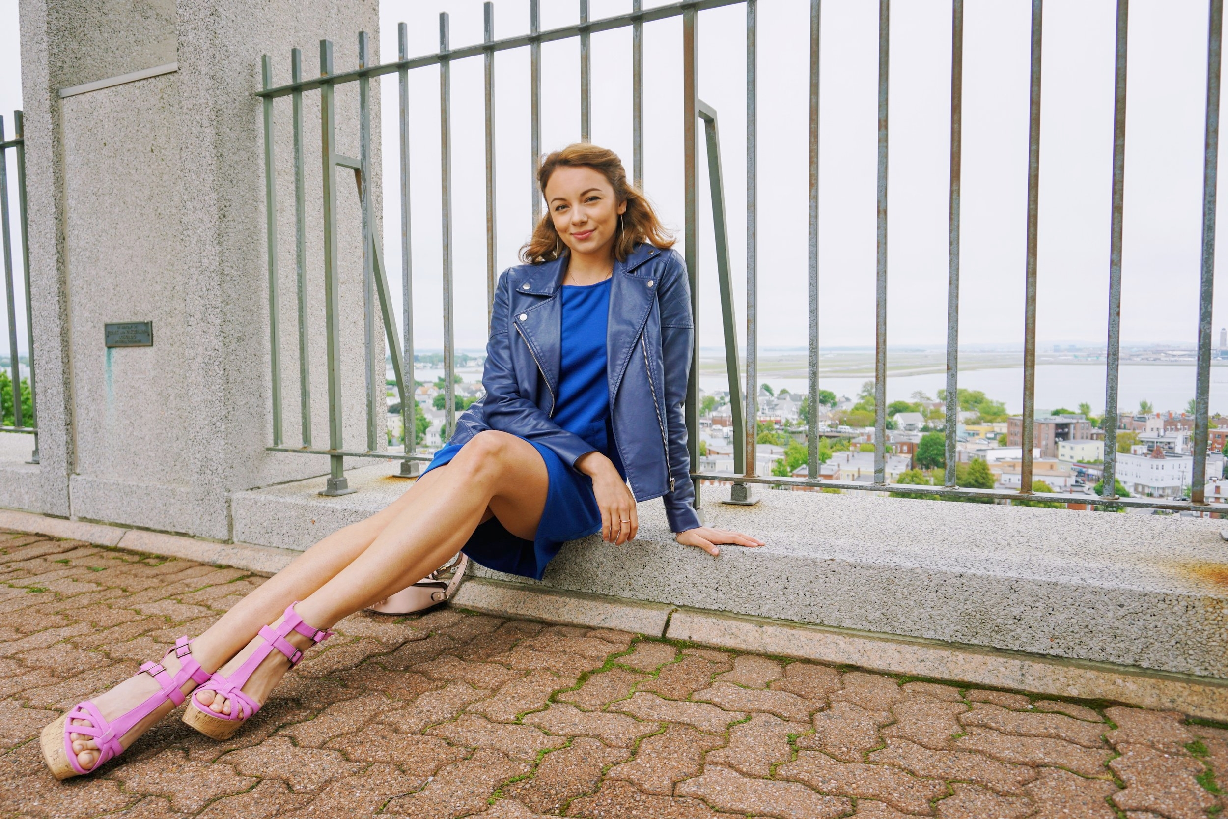 A blogger posing, and wearing blue dress, blue leather jacket, and lavender wedges.