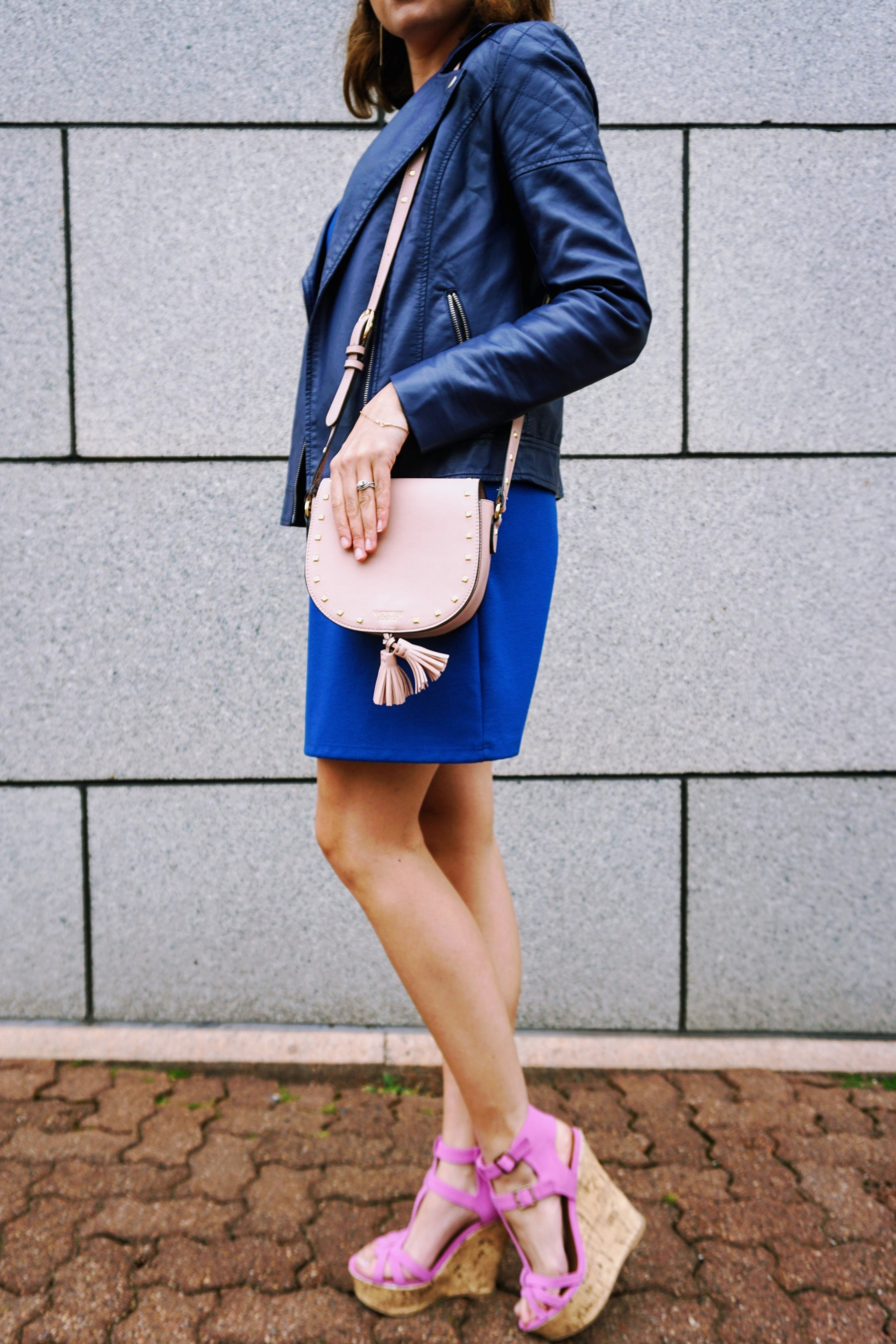 Details of a romantic spring outfit: blue dress, blue leather jacket, lavender wedges, and pink bag.