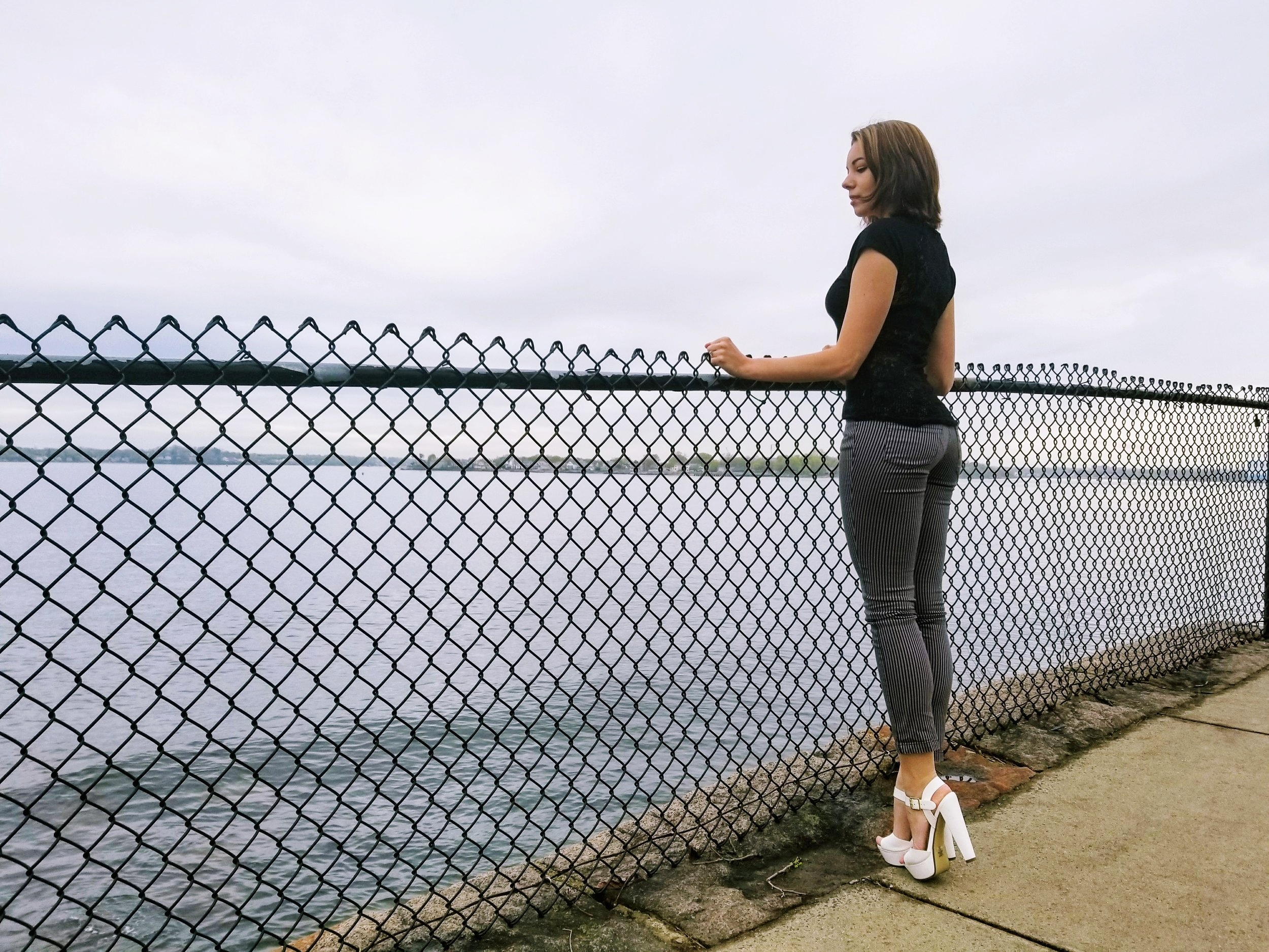 A blogger looking at the ocean, wearing stripped pants, white heels, and black t-shirt.