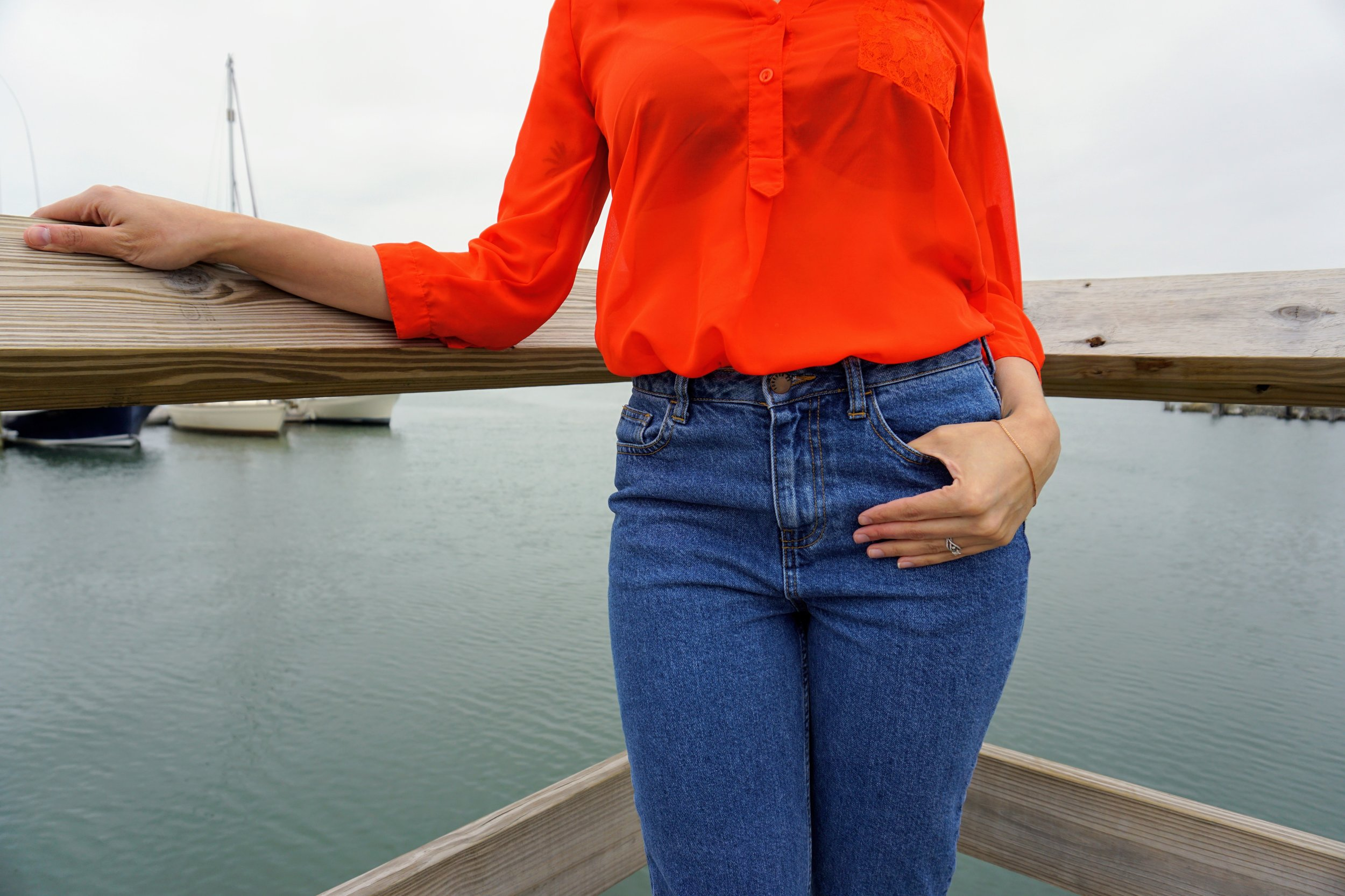 A close-up of an outfit: bright orange blouse, and blue mom jeans.