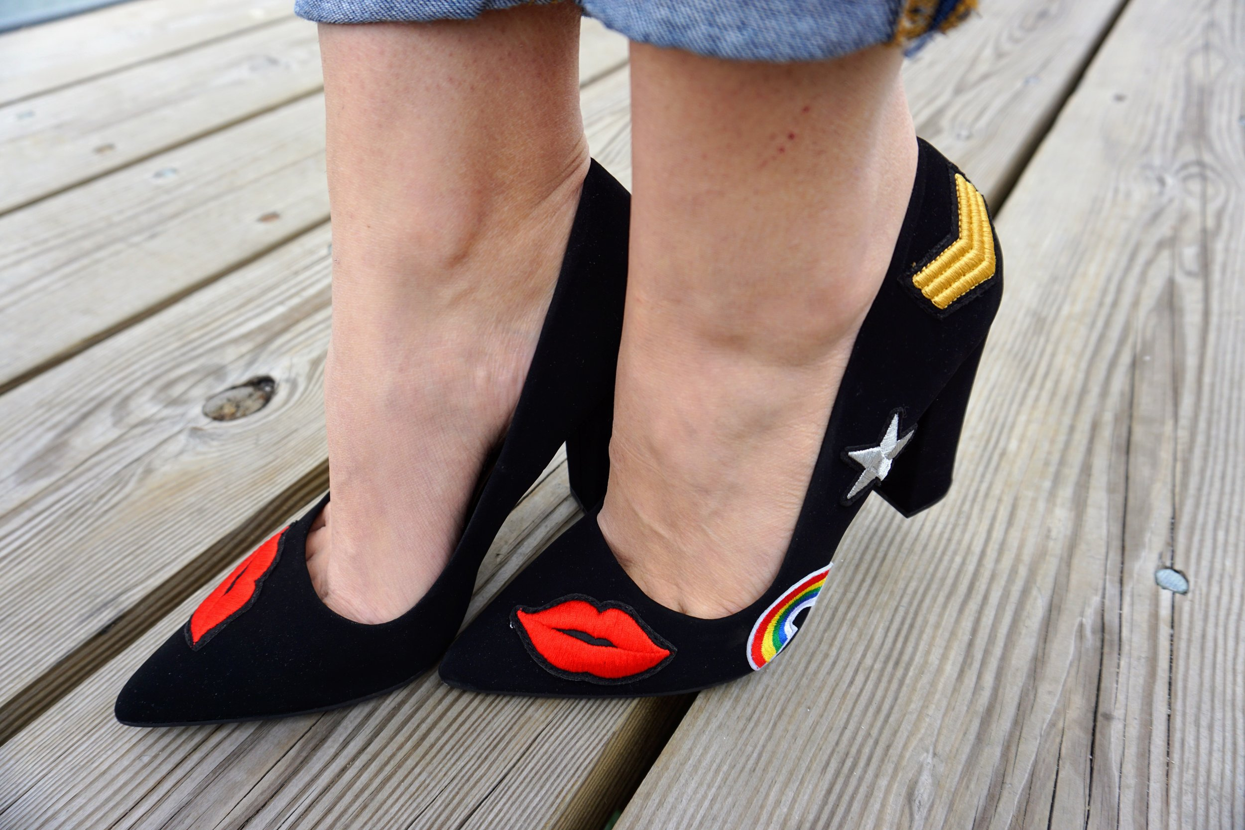 A close up of black heels with hearts, stars and rainbows on them.
