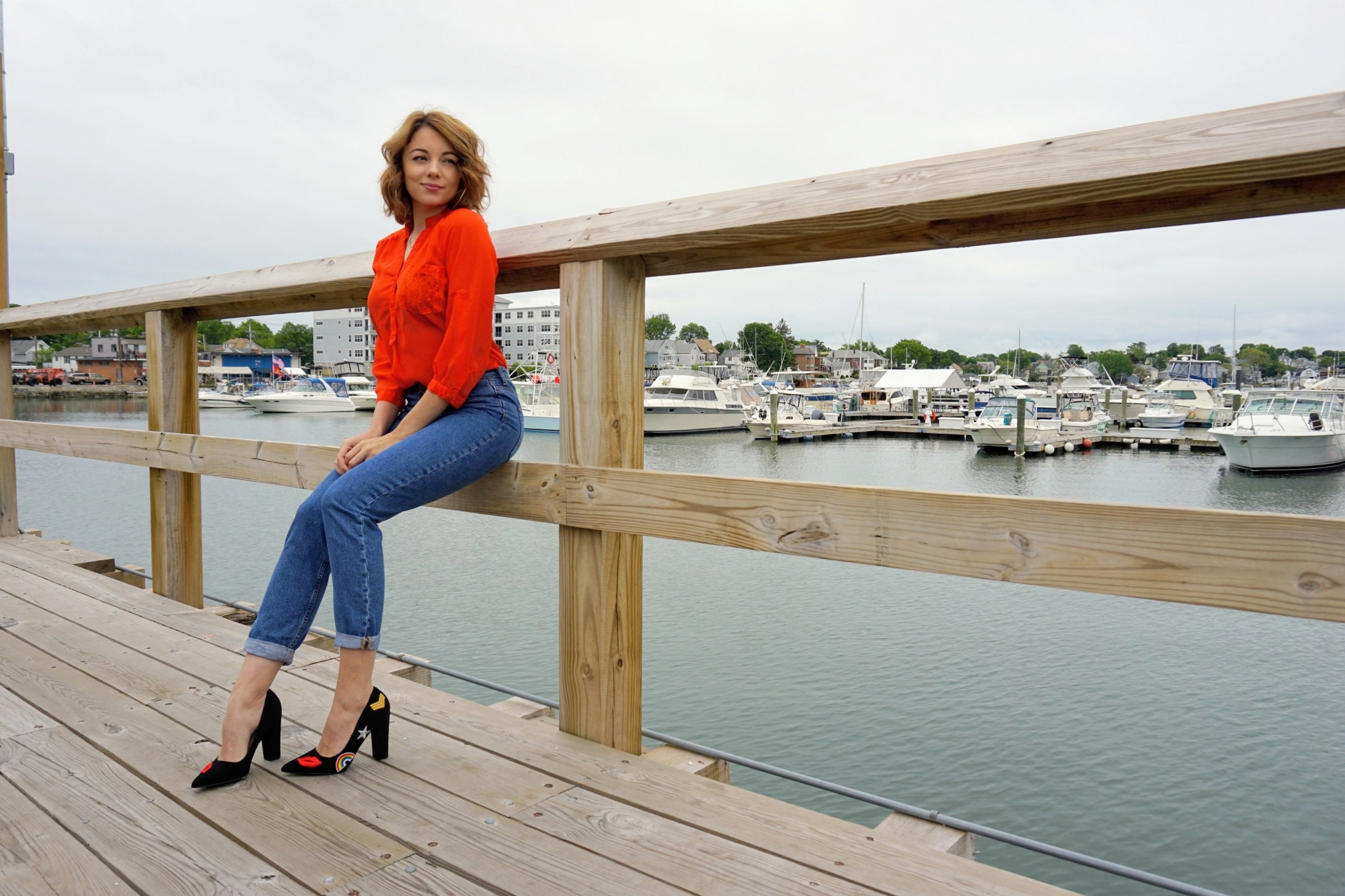 A blogger sitting on the dock with a beautiful view in the back.
