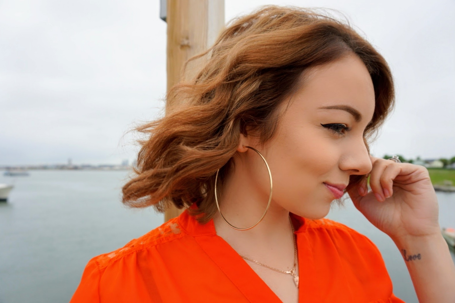 A portrait of a blogger looking to the side, wavy hair, golden hoop earrings, and a bright orange blouse.