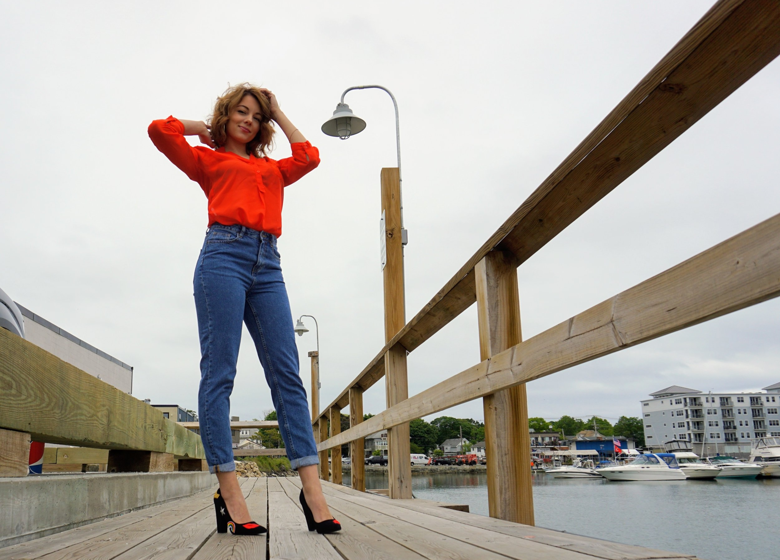 A blogger posing on the dock near the water, wearing a bright orange blouse, tucked in the mom jeans, and black heels with rainbows and hearts on them.
