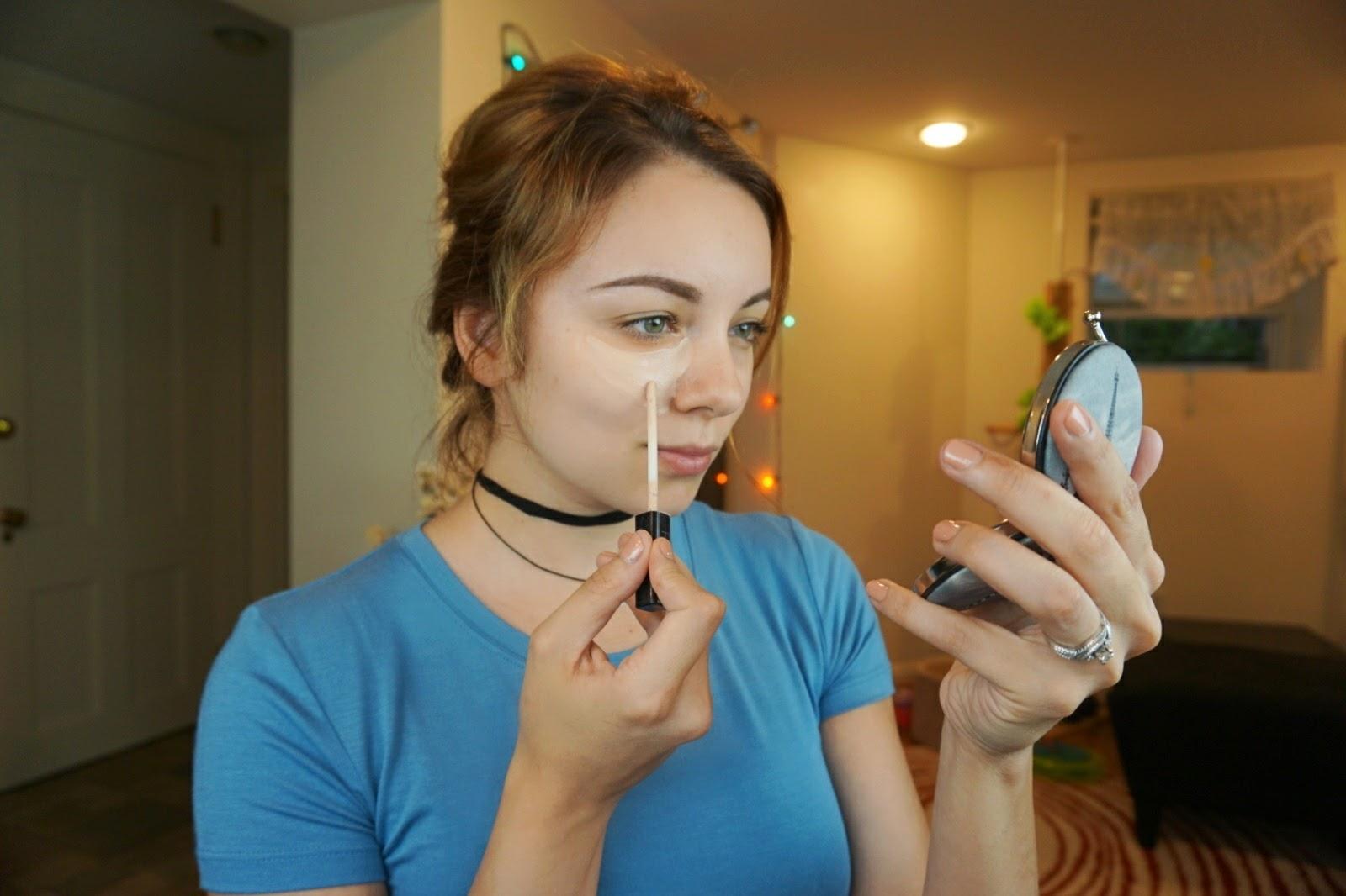 A girl applying concealer on top of peach concealer under her eyes.