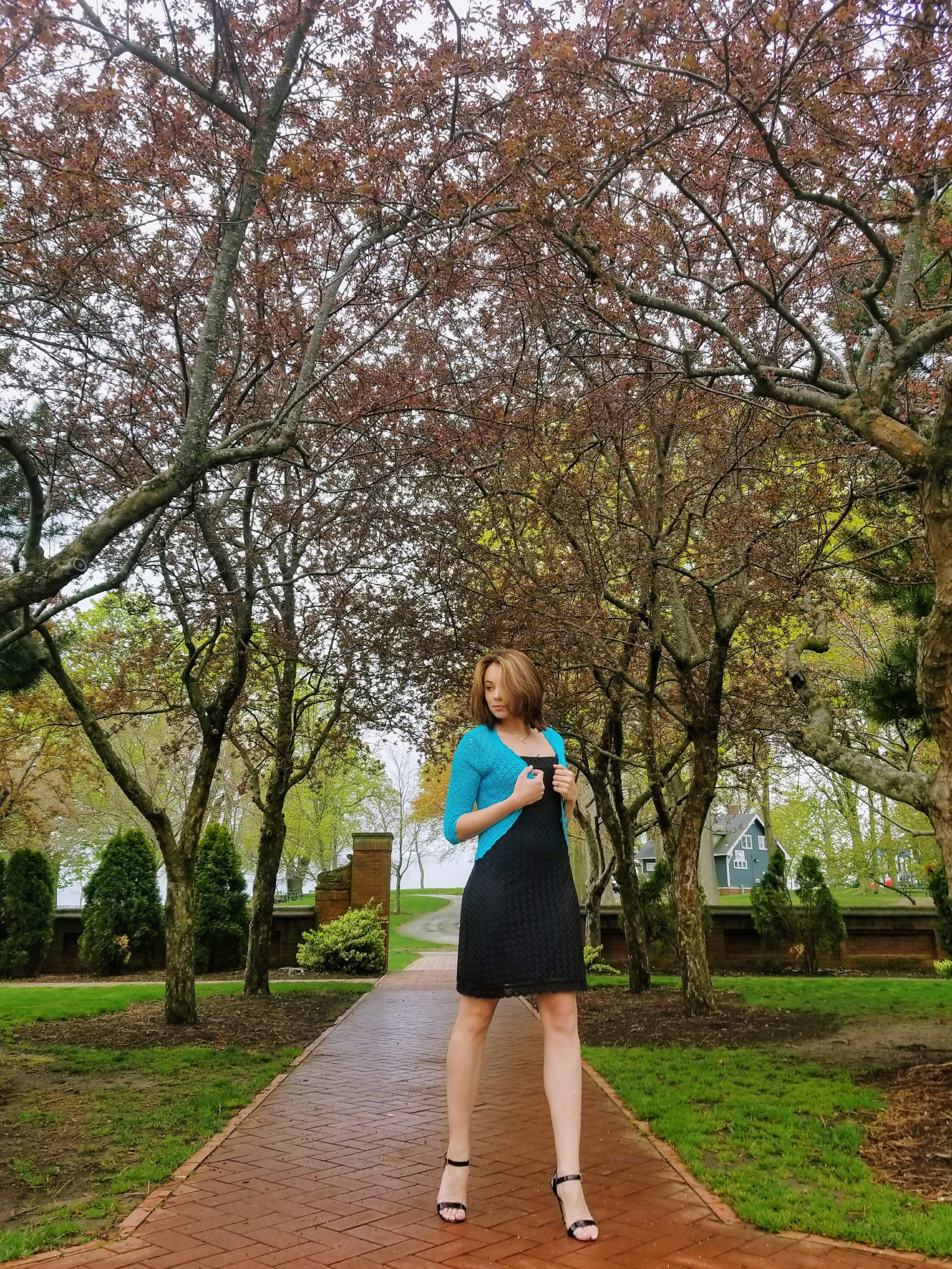 A girl in the garden. She is wearing a little black dress, blue cover-up and black heels.