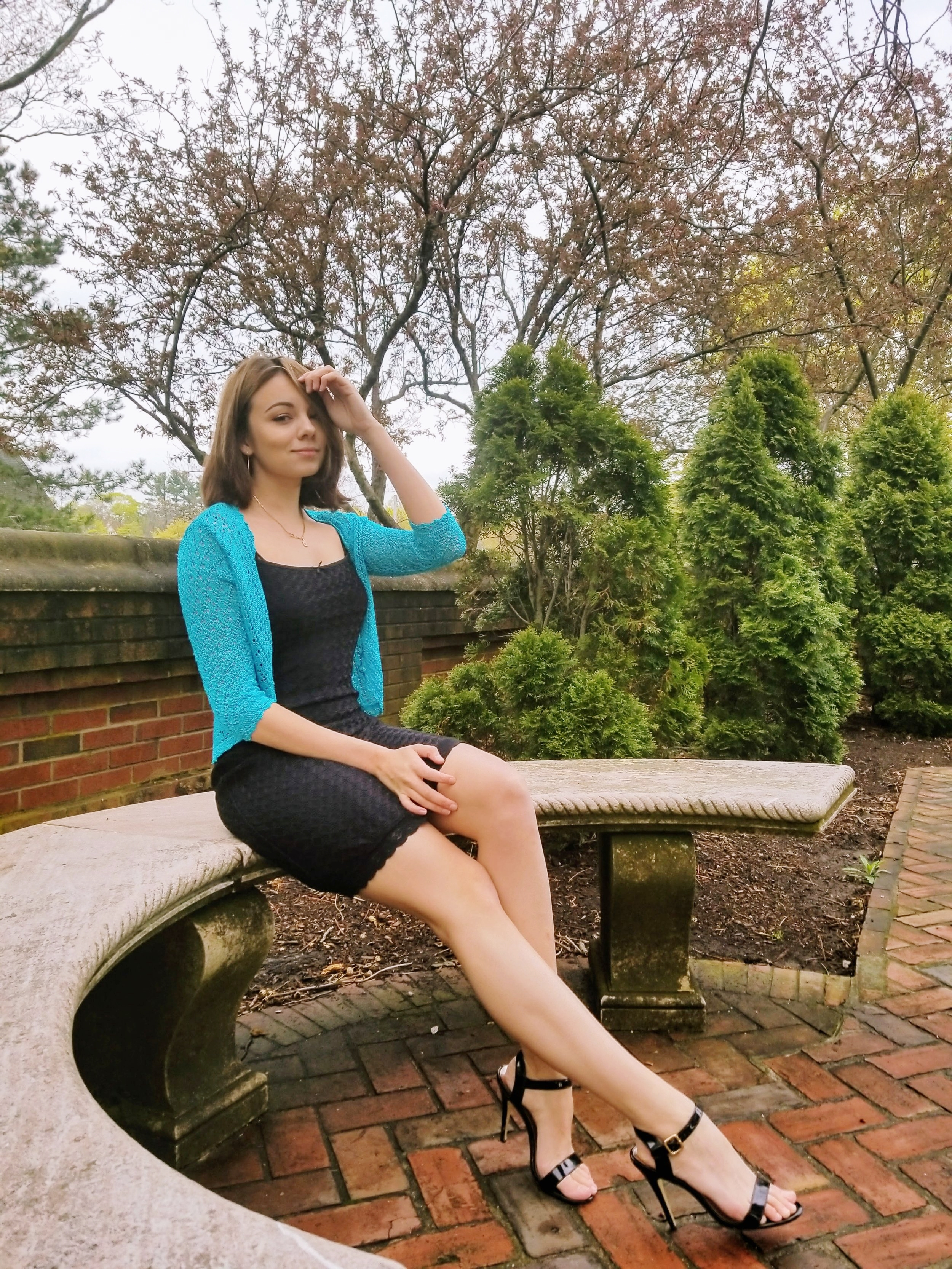 A blogger wearing a black dress, blue crotchet cover-up and black heels.
