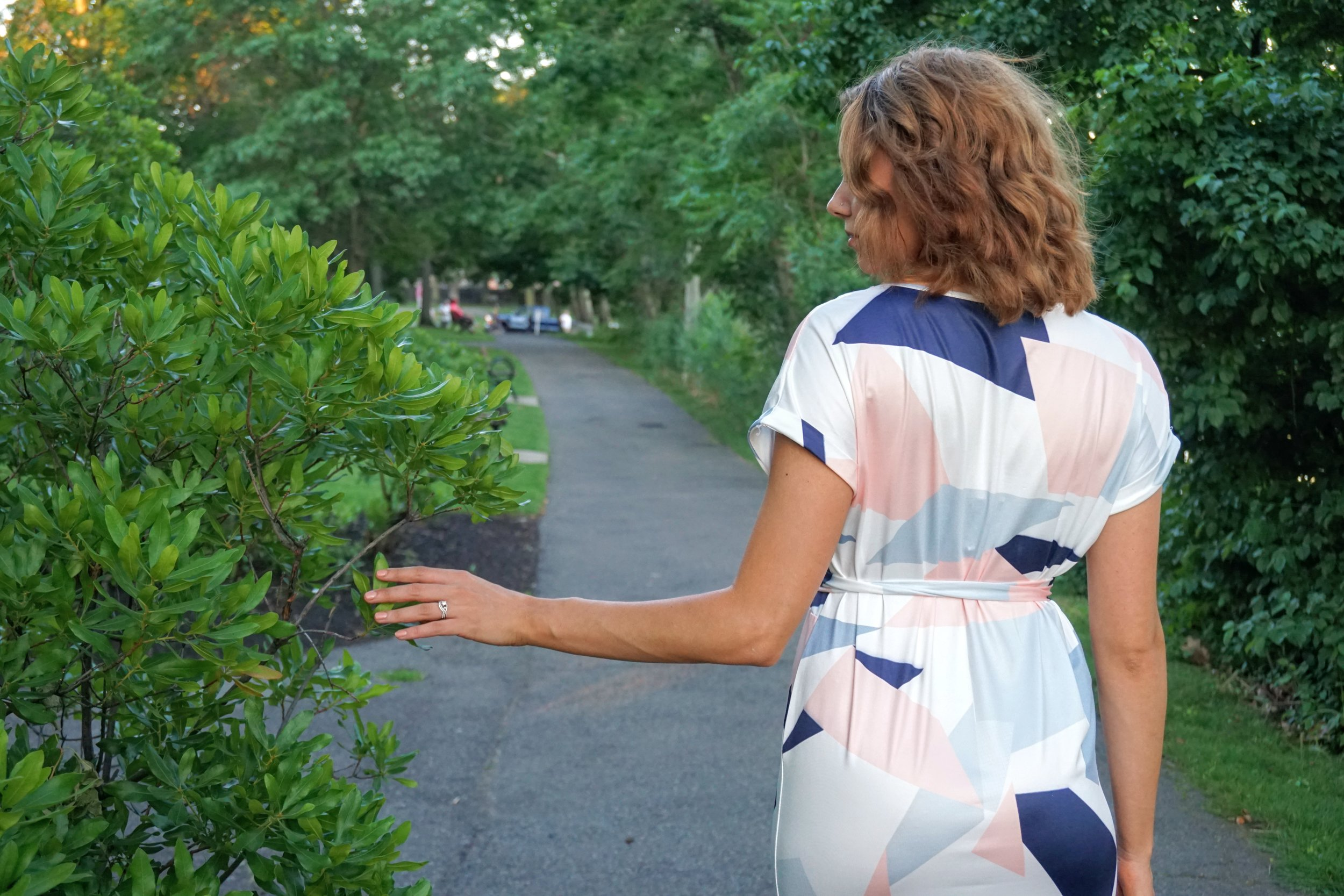 A photo of a girl turning her back on the camera, wearing a pink, white and blue dress.