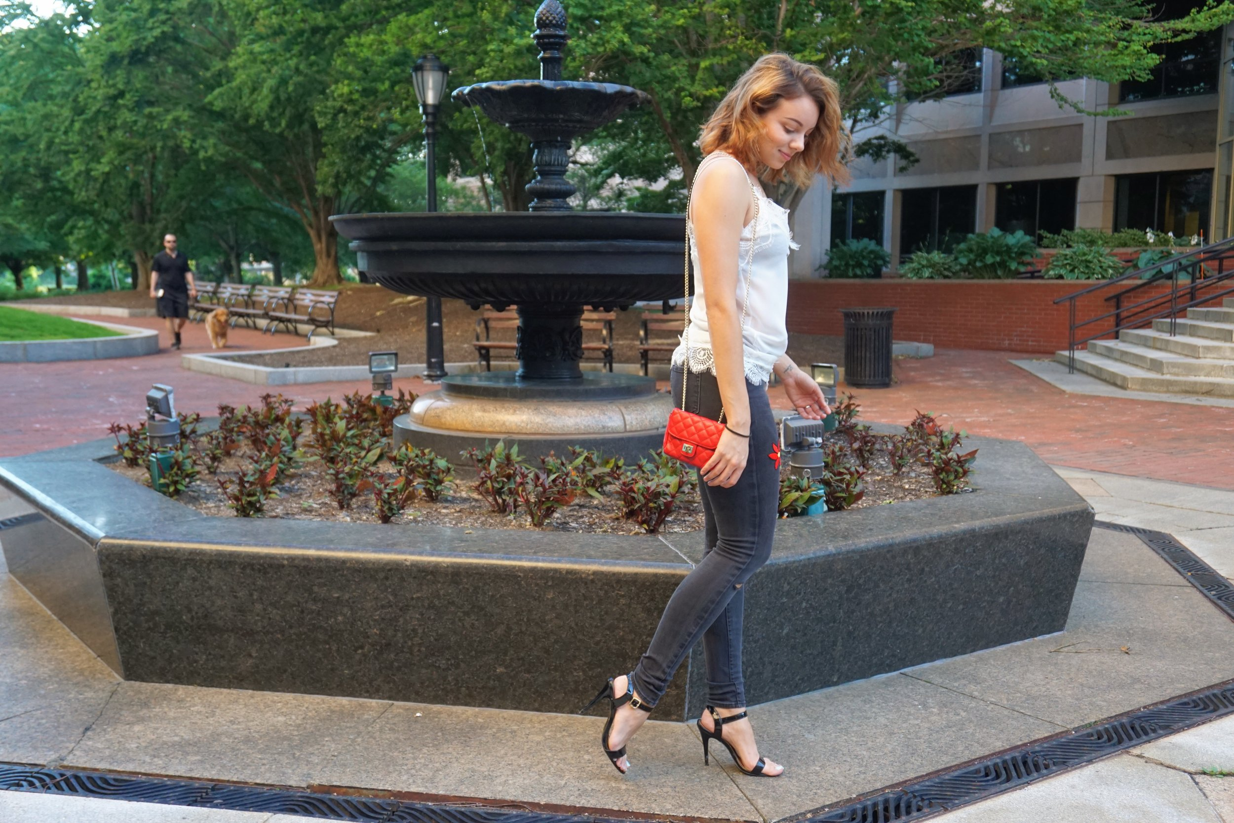 Summer look: white lace top, black ripped jeans, black choker, black sandal heels, and red little bag.