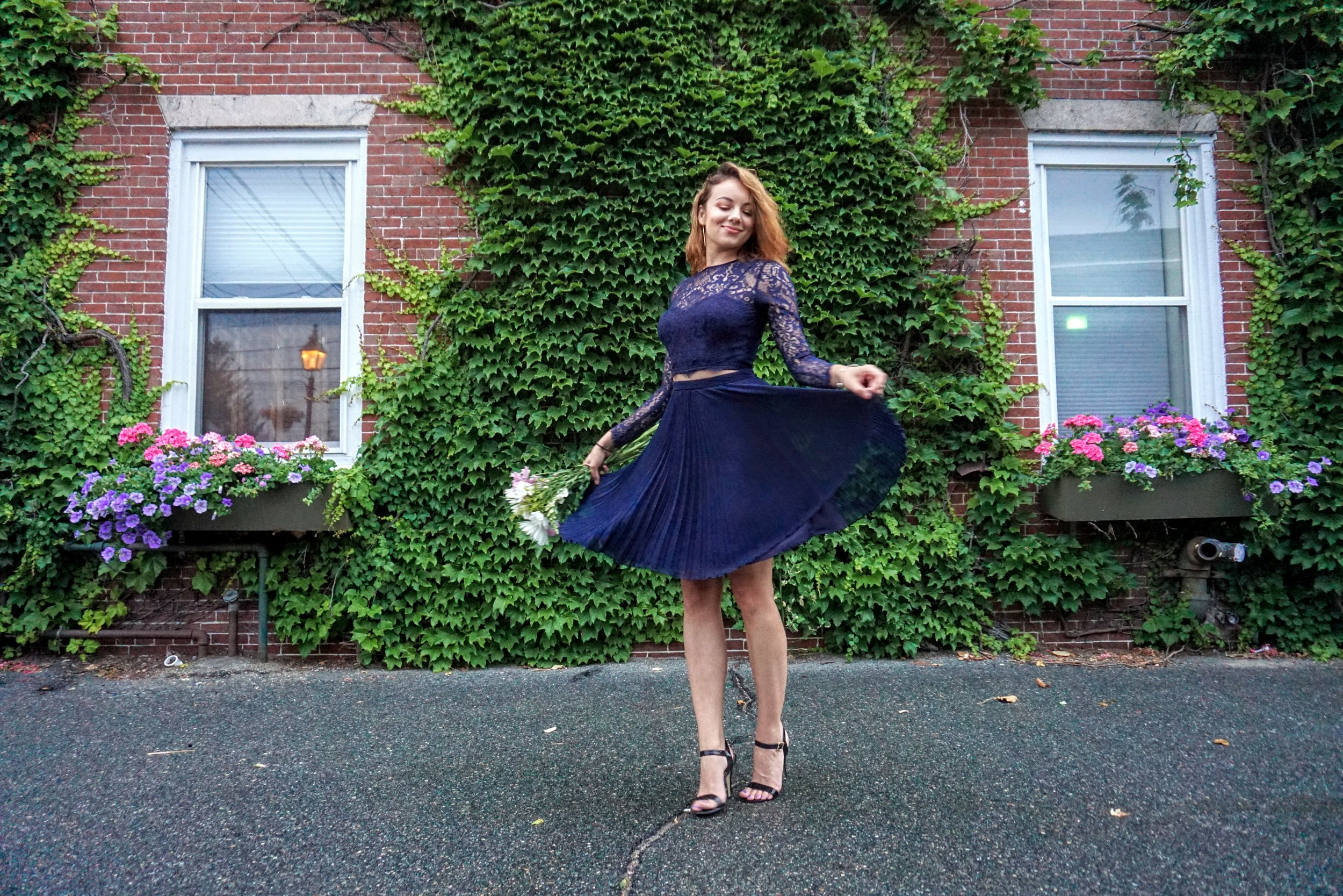 A photo of a girl twirling in her dark blue dress set.