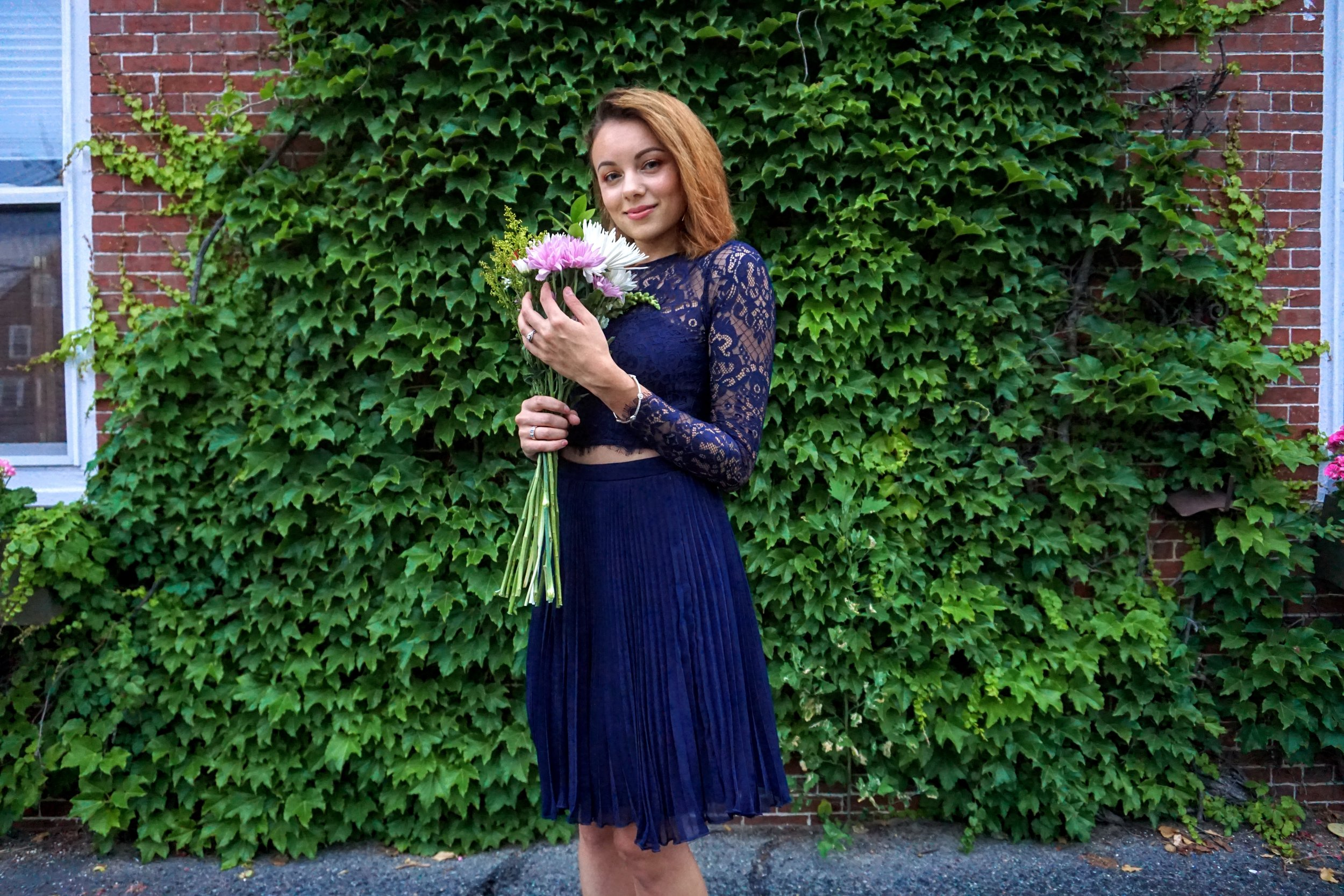 A photo of a girl holding flowers and wearing a dress set of lace crop top and a skirt.