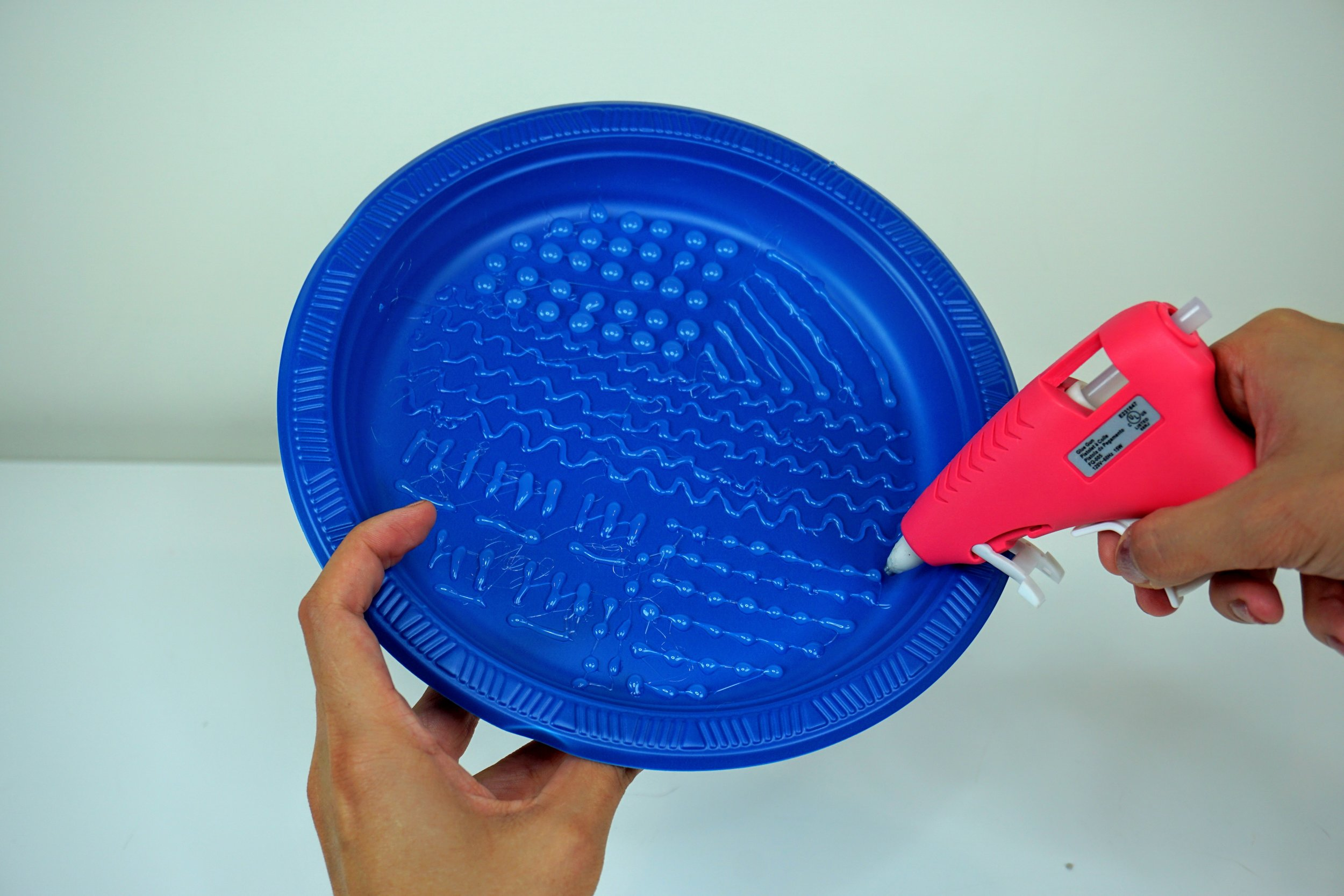 Making squiggly and vertical lines, dots on the blue plastic plate by a glue gun to make a diy brush cleaning mat.