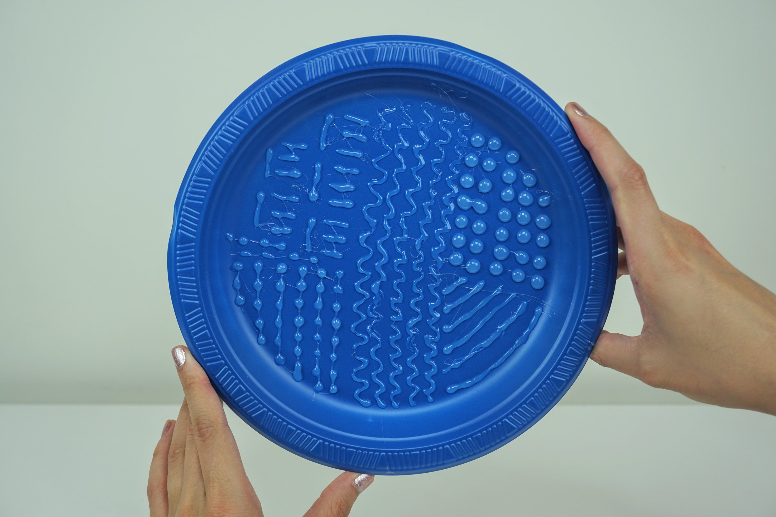 A DIY makeup brushes cleaning mat: a blue plastic plate that has squiggly lines on it.