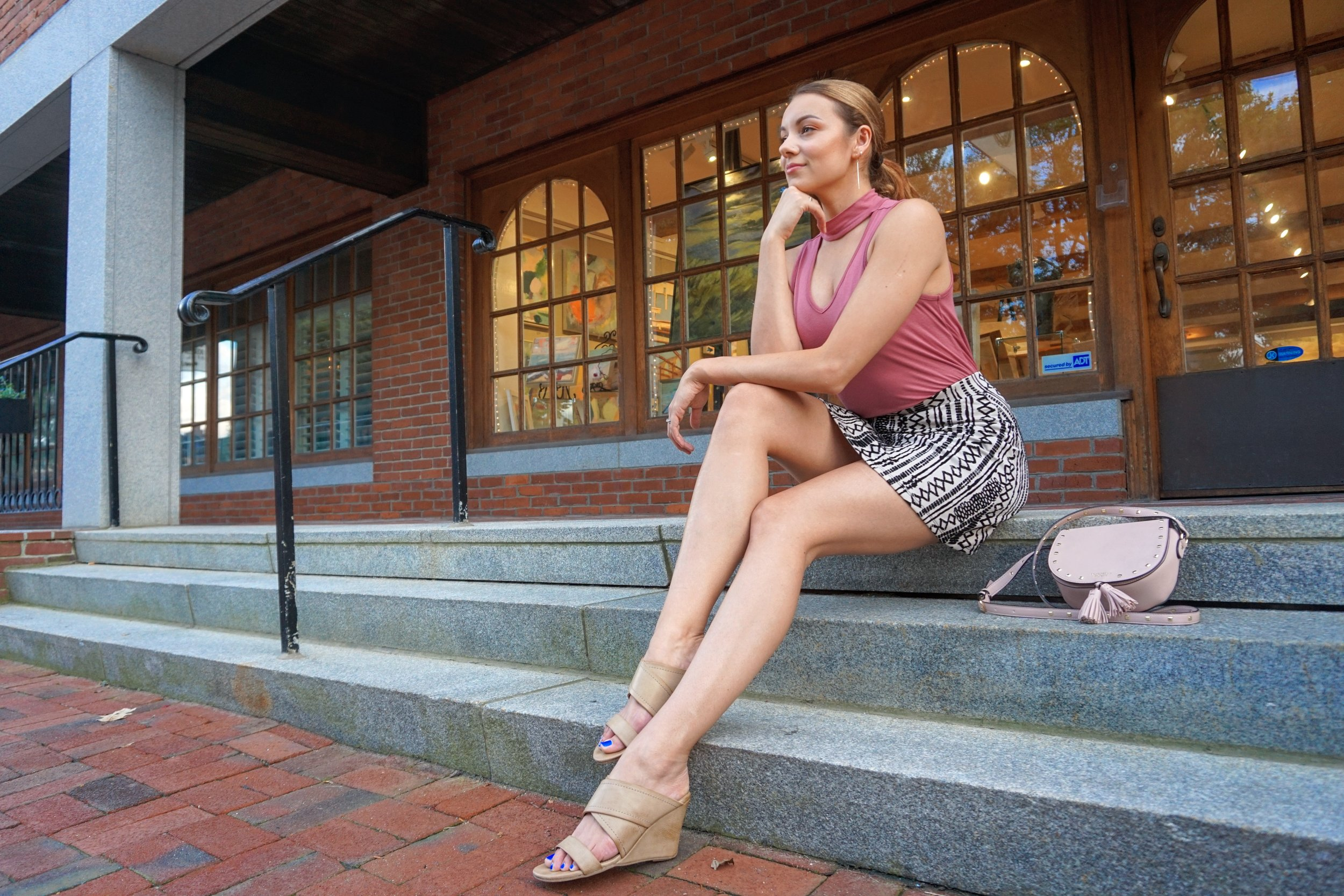 A girl sitting on the stair, wearing a pink choker top, a skirt, nude wedges.