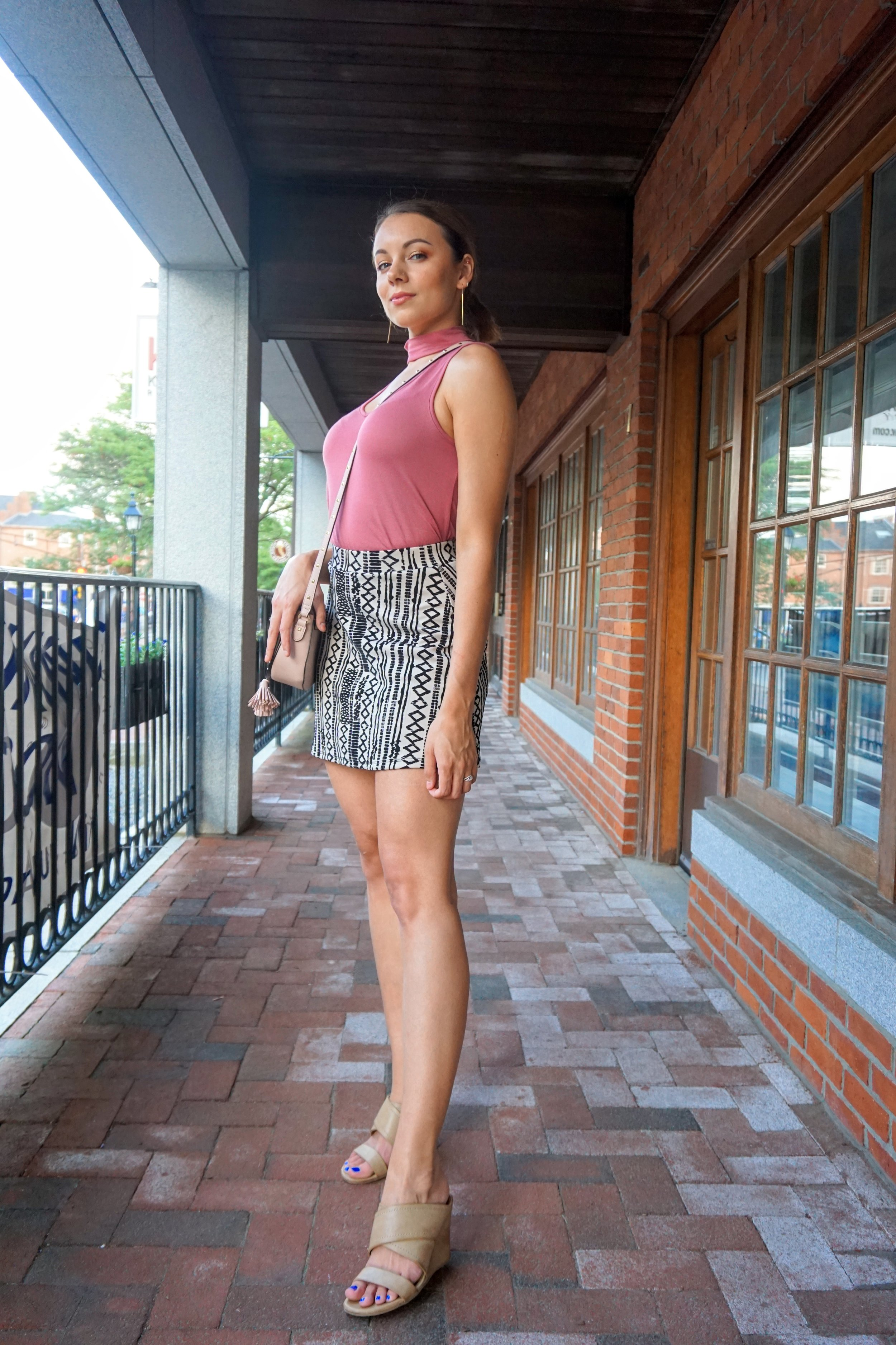 A blogger posing near the shops. She is wearing a pink choker top, nude and black skirt, nude wedges, and carries a pink victoria's secret bag.