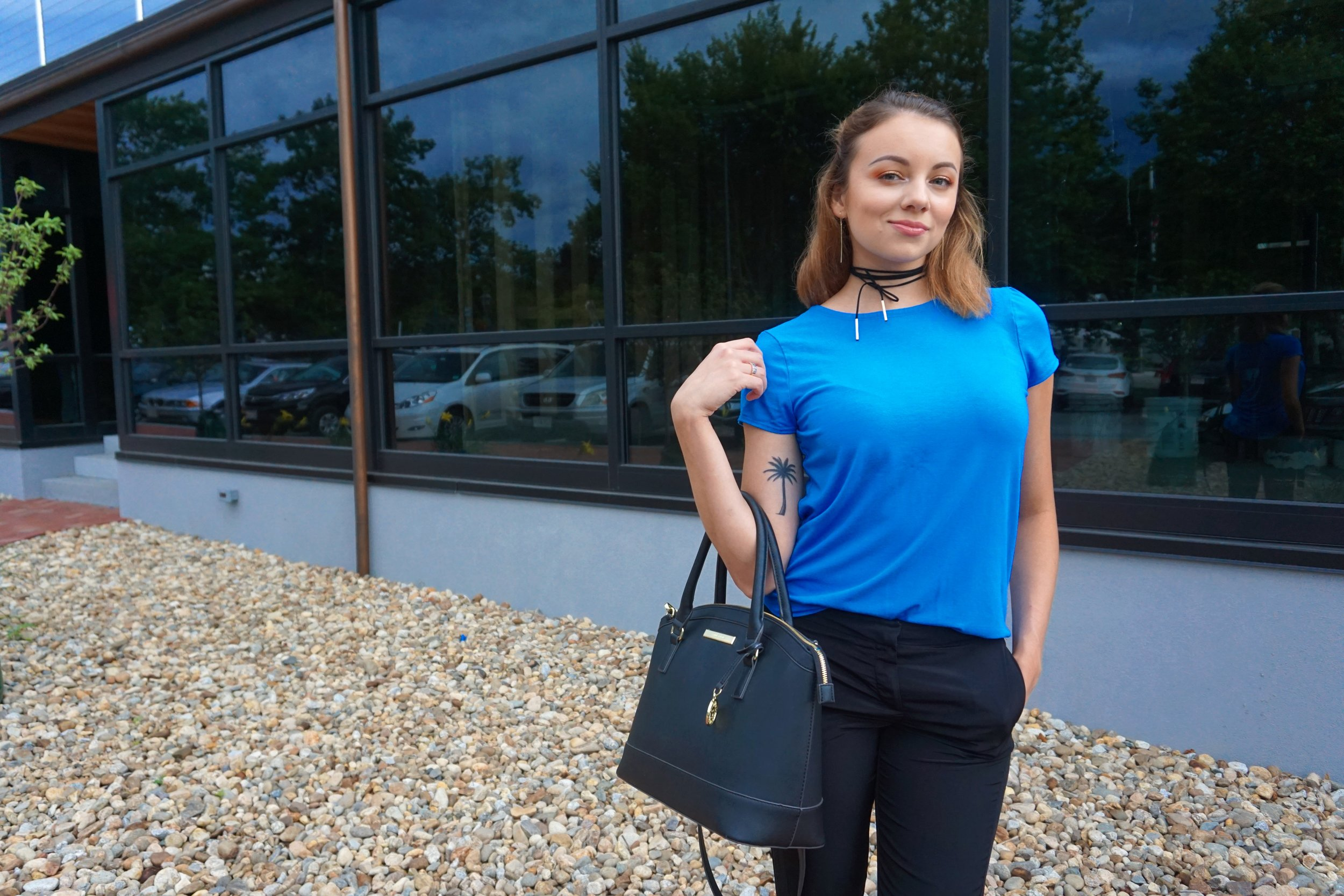 A girl posing by the office. She is holding a big black bag, and wearing a baby blue top and black pants.
