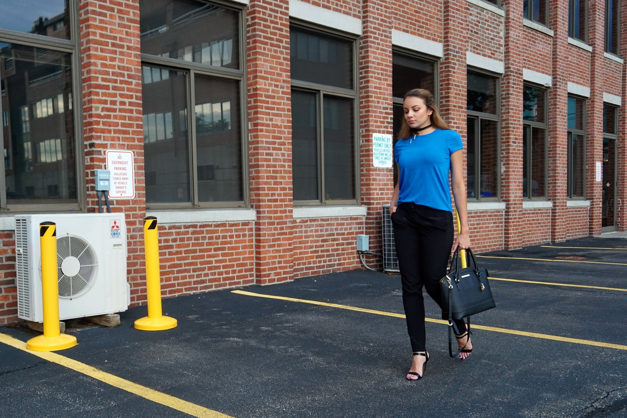 A walking shot of a blogger. She is wearing a blue top, black pants, high heeled sandals, black bag, and a choker.
