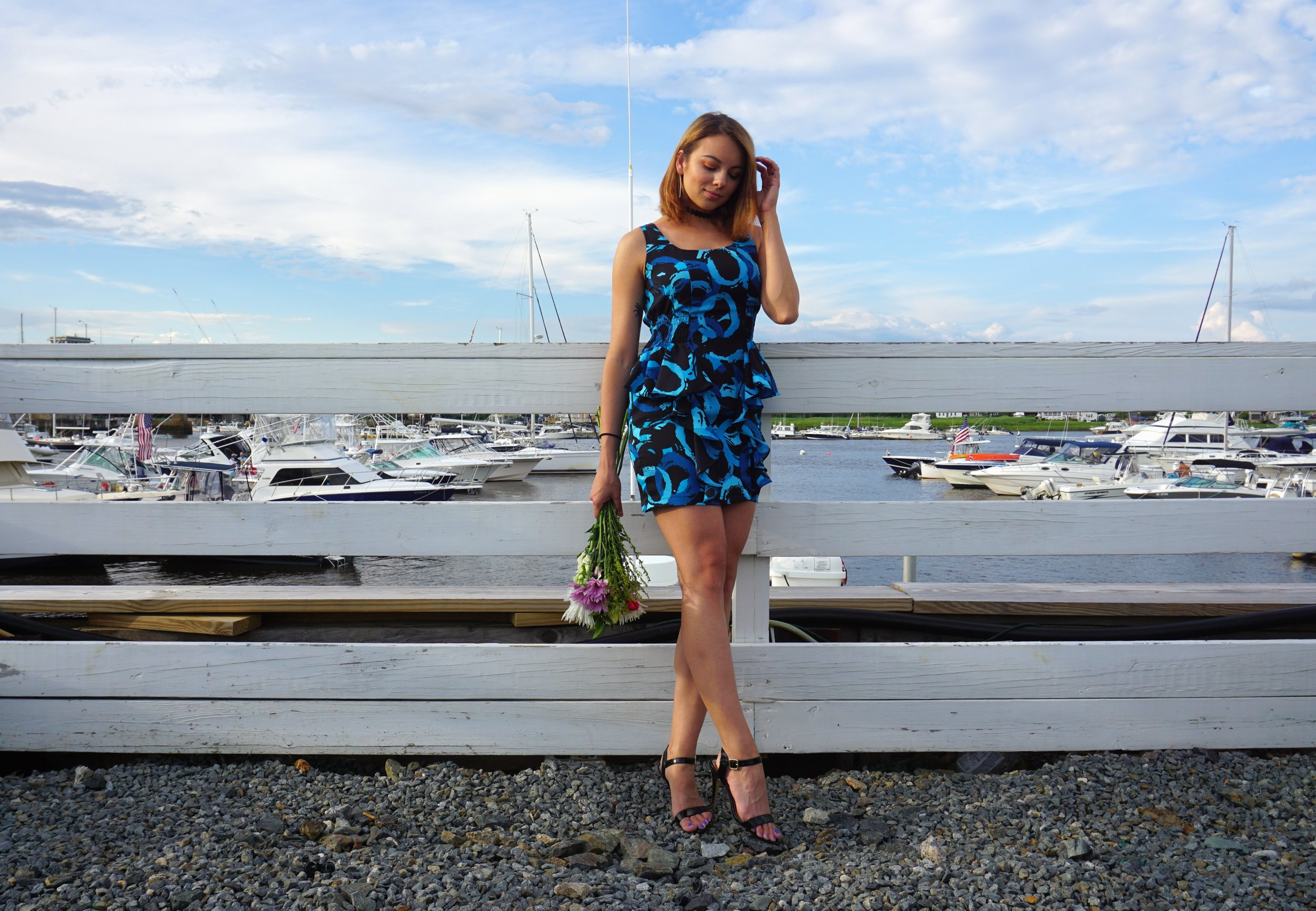 Girl standing on the pier with flowers, wearing a short blue summer dress, high heeled sandals, and a black choker.