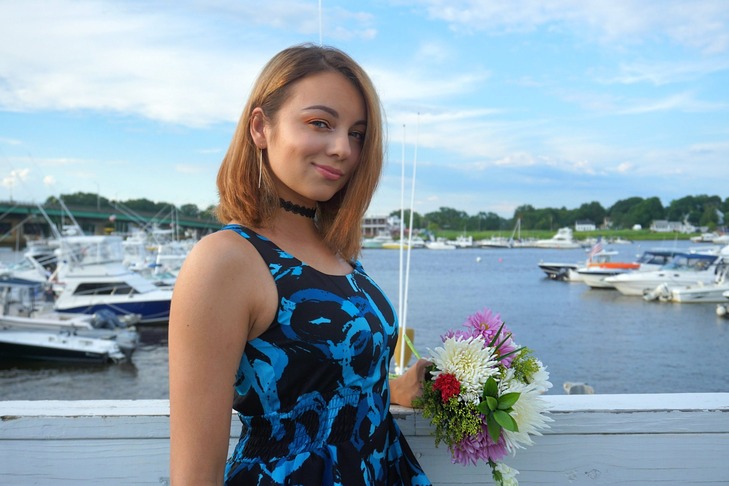 A blogger by the pier holding flowers.