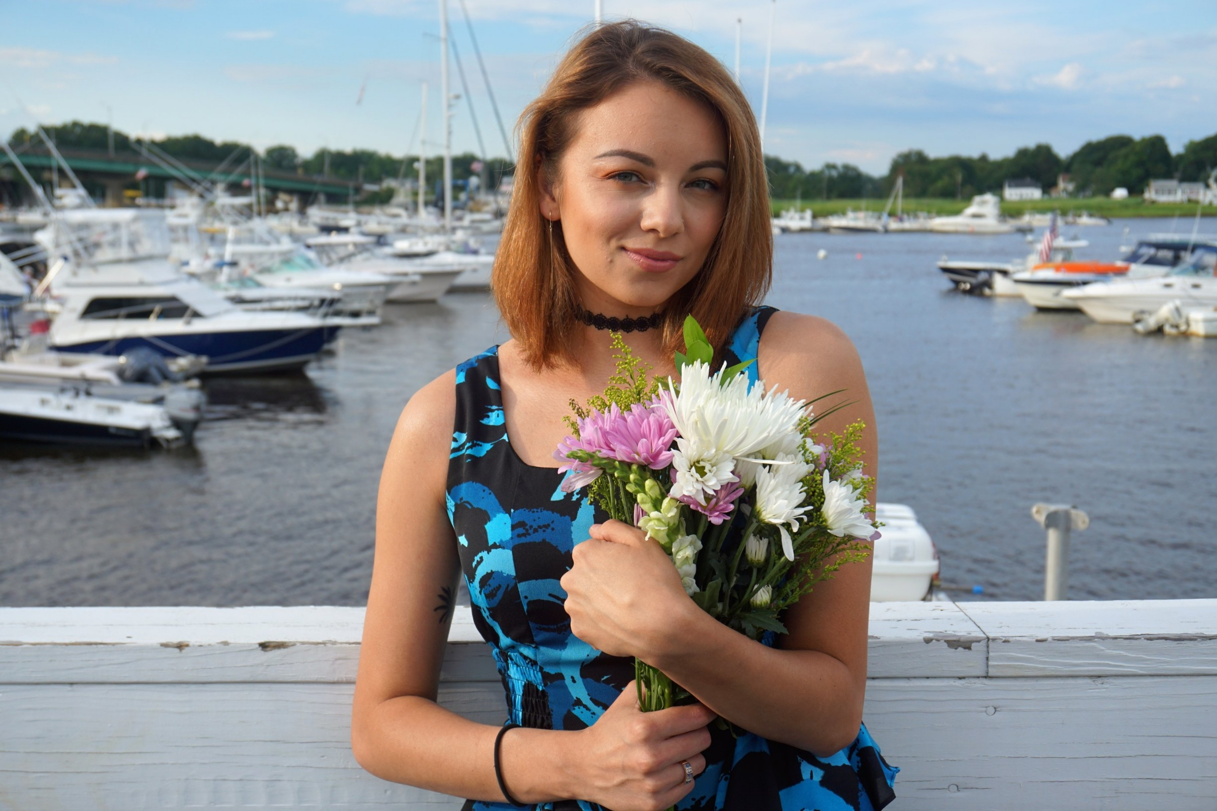 A portrait of a girl holding flowers on the pier.