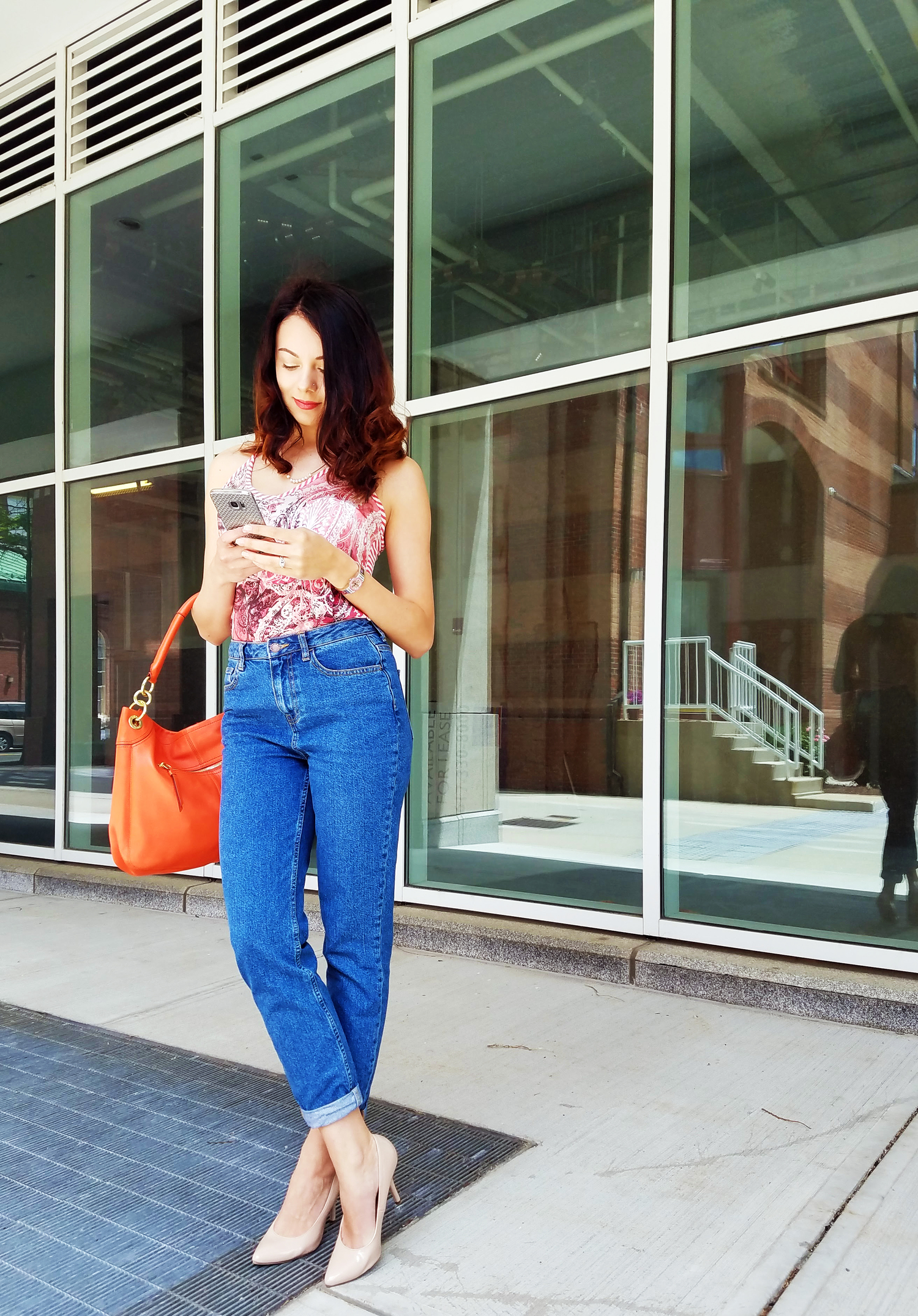 A girl wearing colourful top tucked into mom jeans, and nude heels.