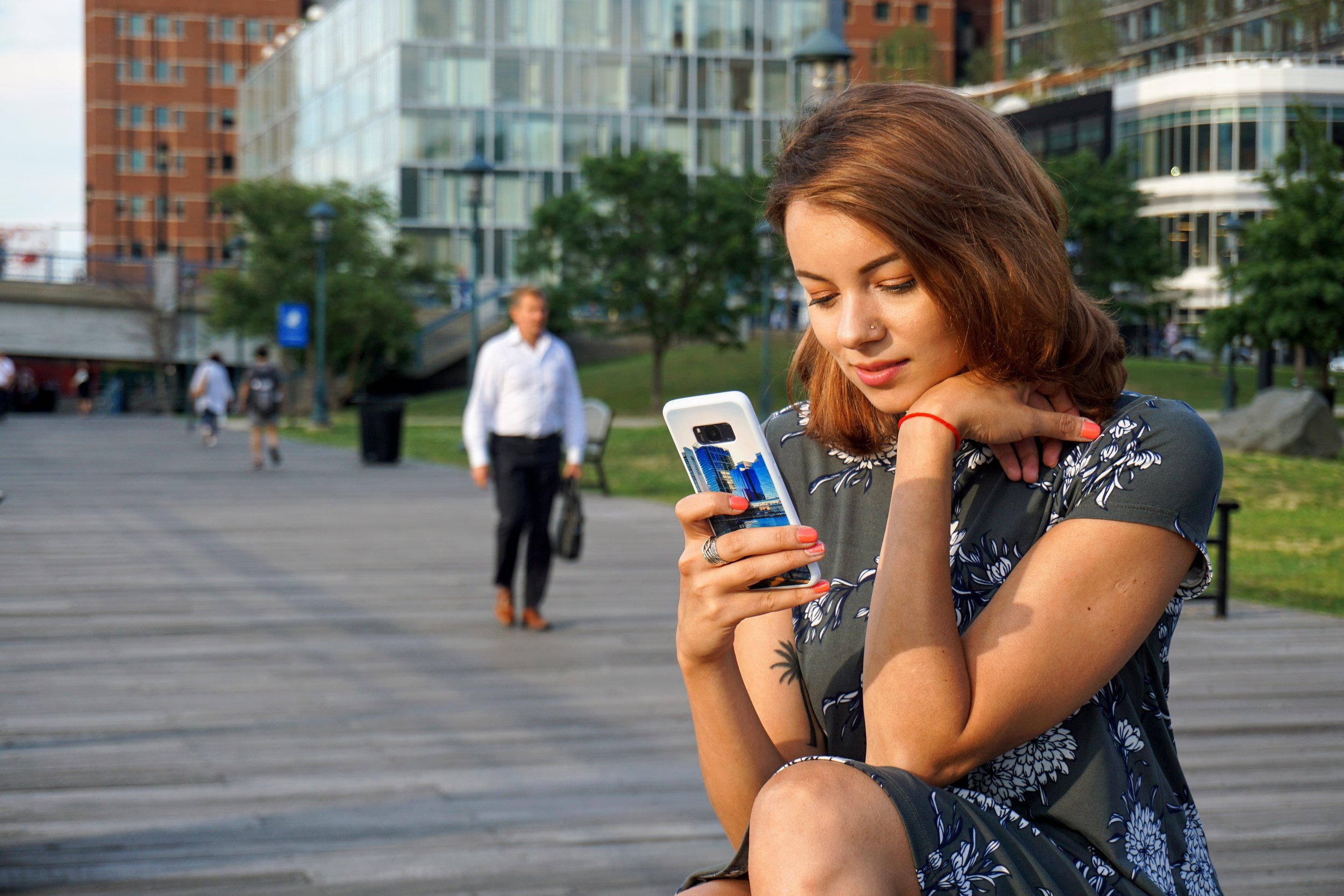 A lifestyle blogger posing and looking at her phone in Boston.