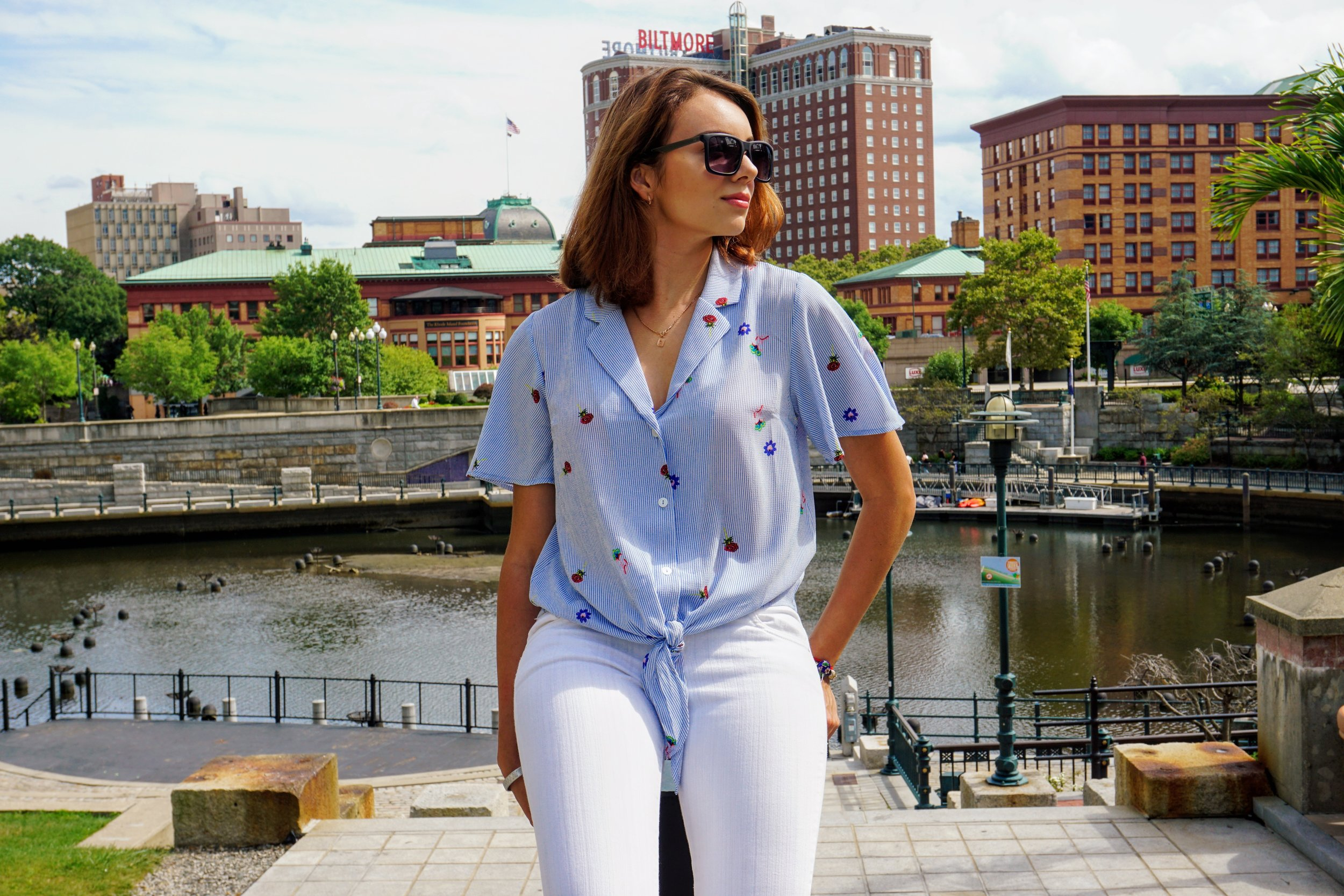 A blogger wearing a blue blouse, white jeans, and posing in Providence, Ma.