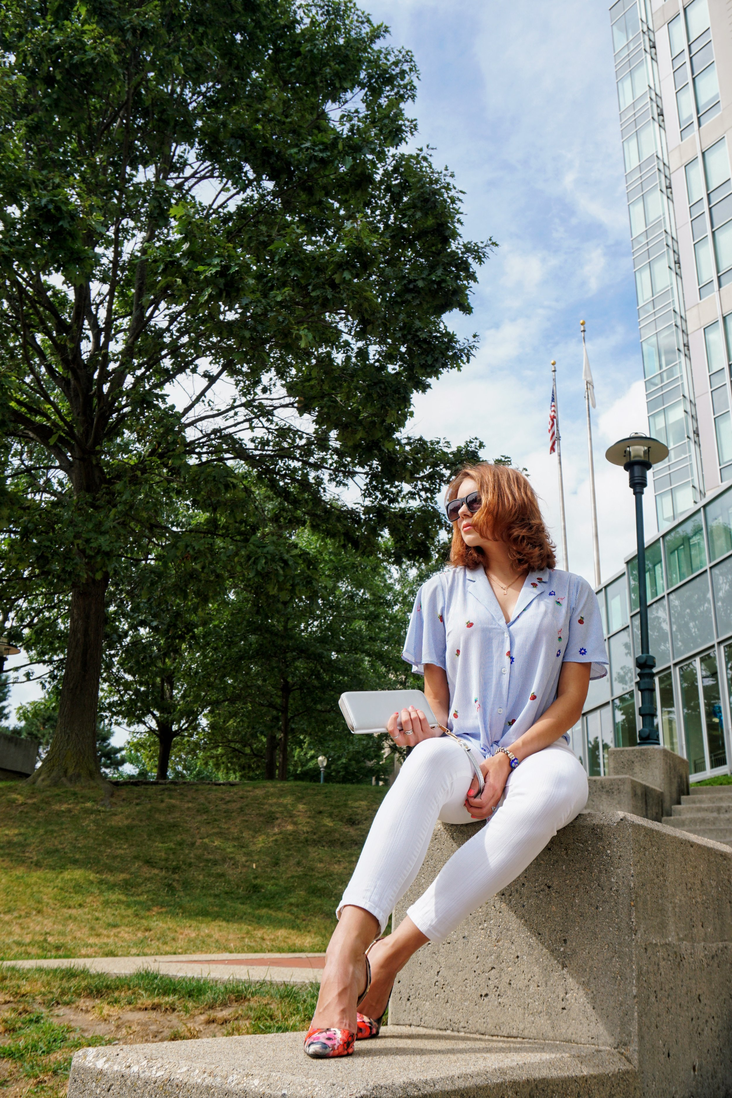 Outfit inspiration: blue flowy blouse, white jeans, gray clutch, and colourful heels.