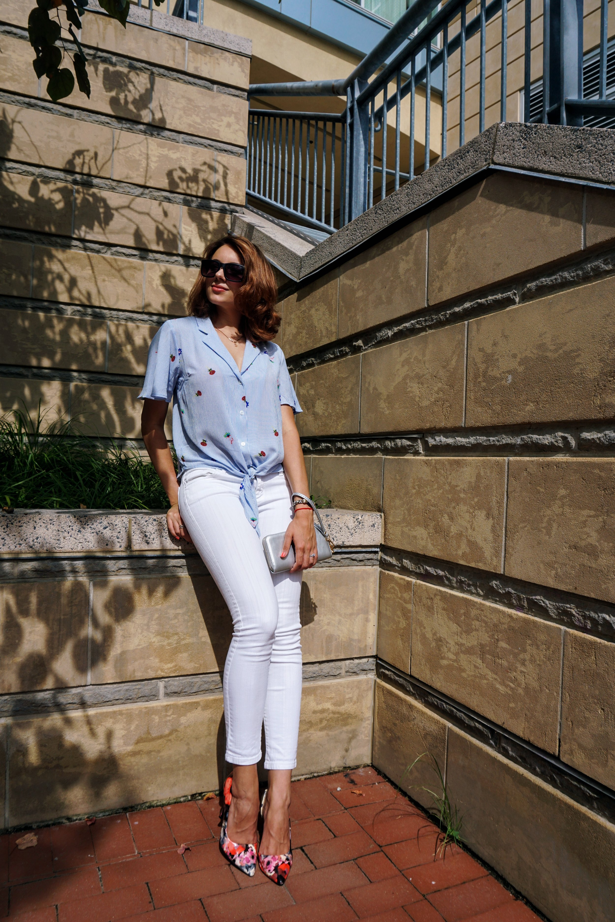 A fashion blogger posing in a summer outfit: blue blouse, white denim capris, colourful heels.
