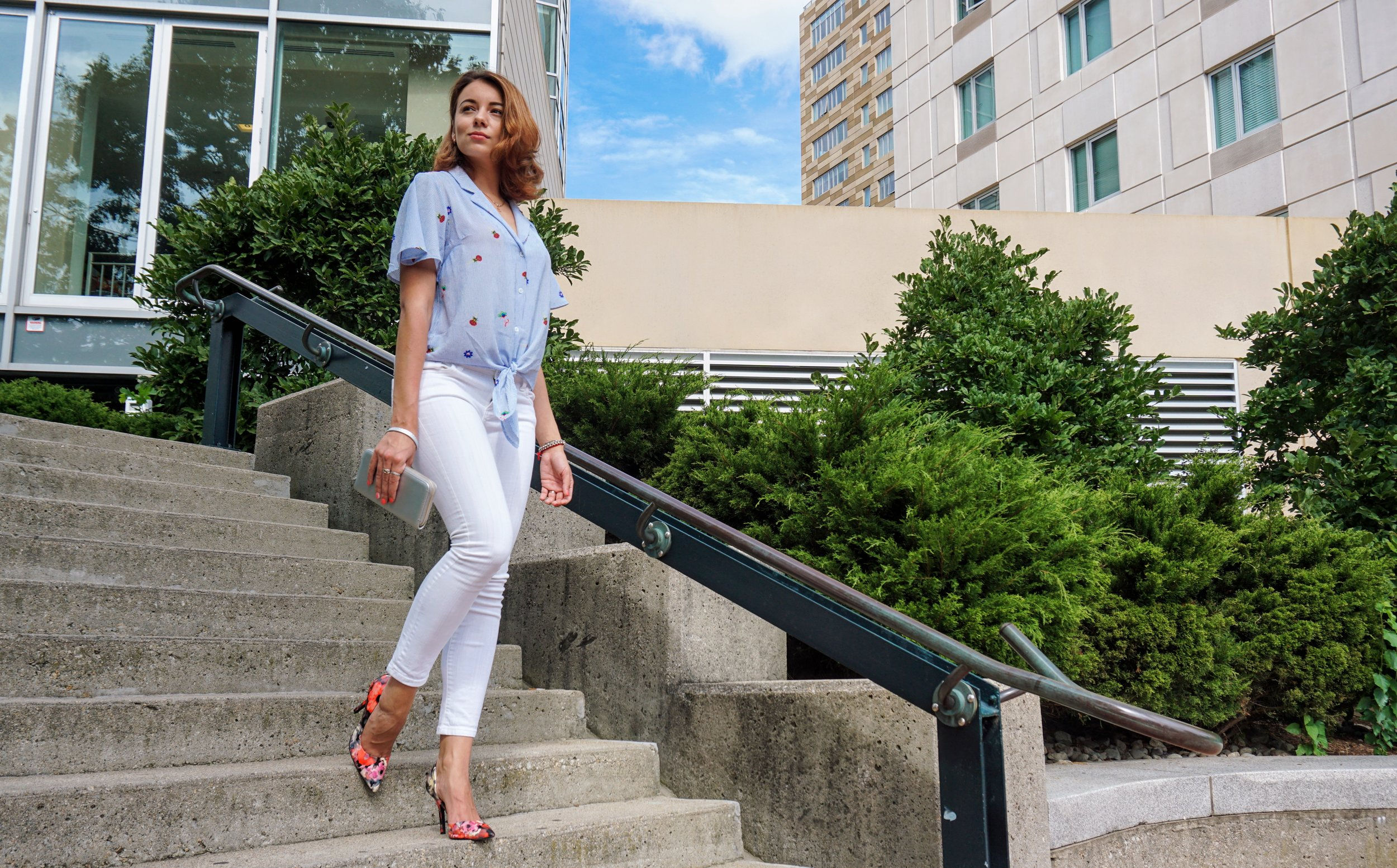 A fashion blogger walking down the stair in a summer white and blue outfit.