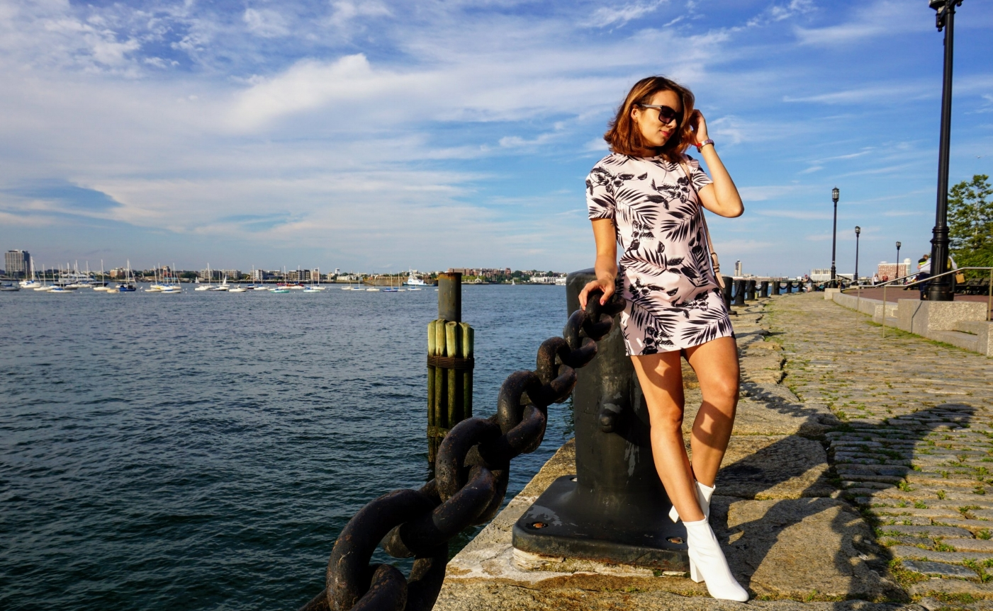 A fashion blogger standing by the Boston river, and wearing a pink dress, white boots, and holding a pink Victoria's Secret crossover bag.