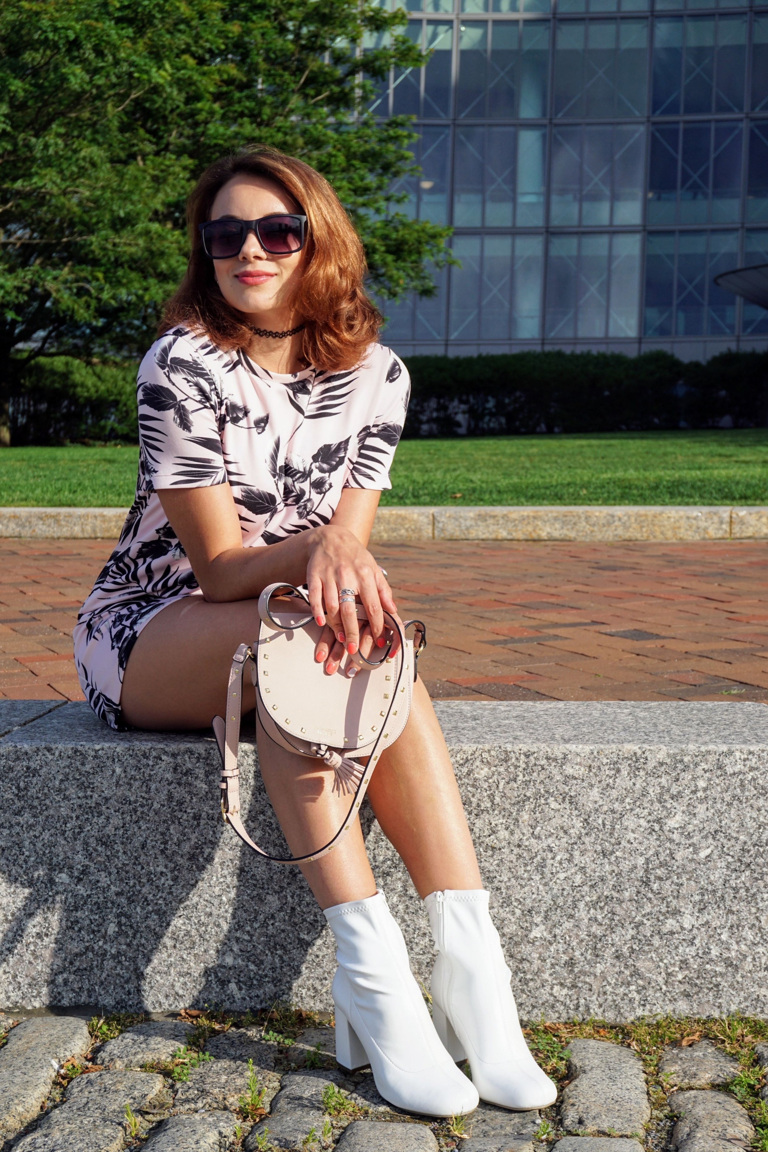 A fashion blogger sitting on the concrete bench, wearing a pink dress, white boots, and a pink victoria's secret bag.