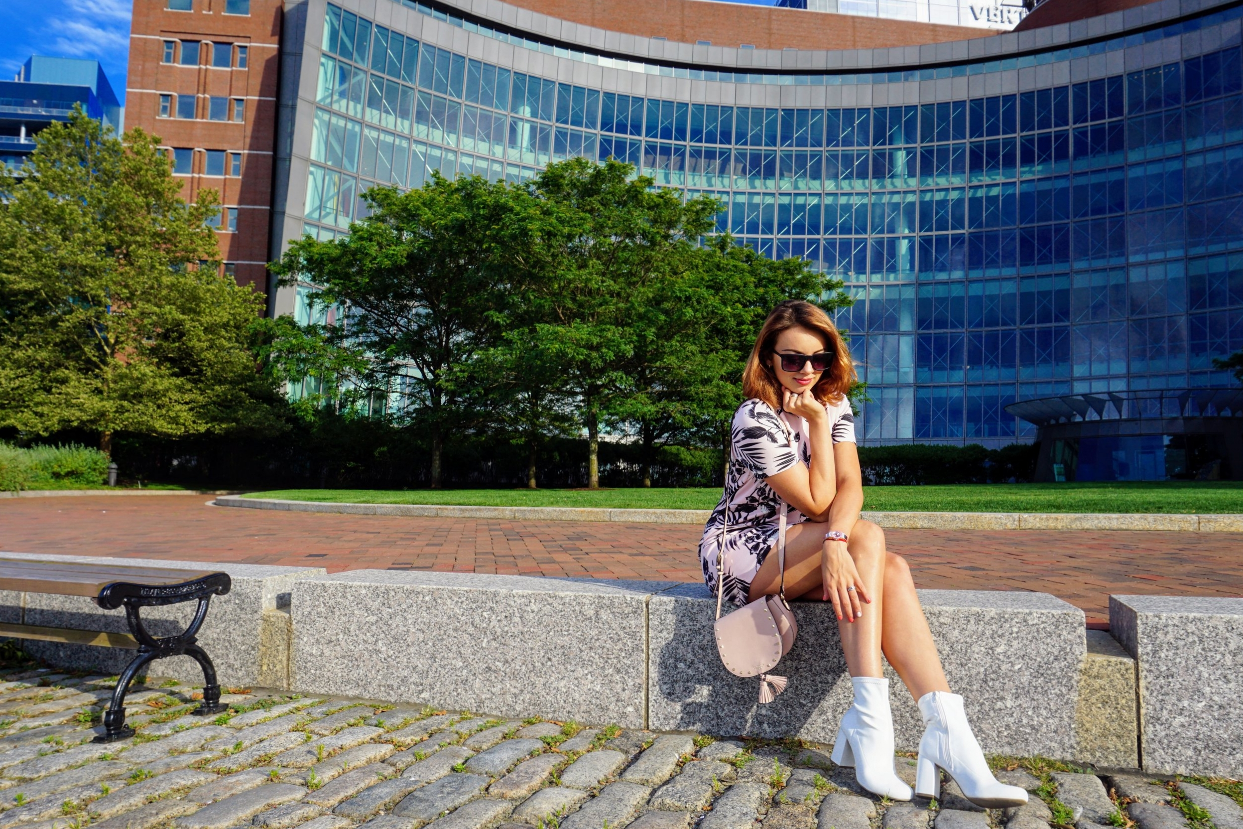 A blogger sitting near one of the buildings in Boston, wearing a summer outfit, pink dress, pink purse, and white boots.