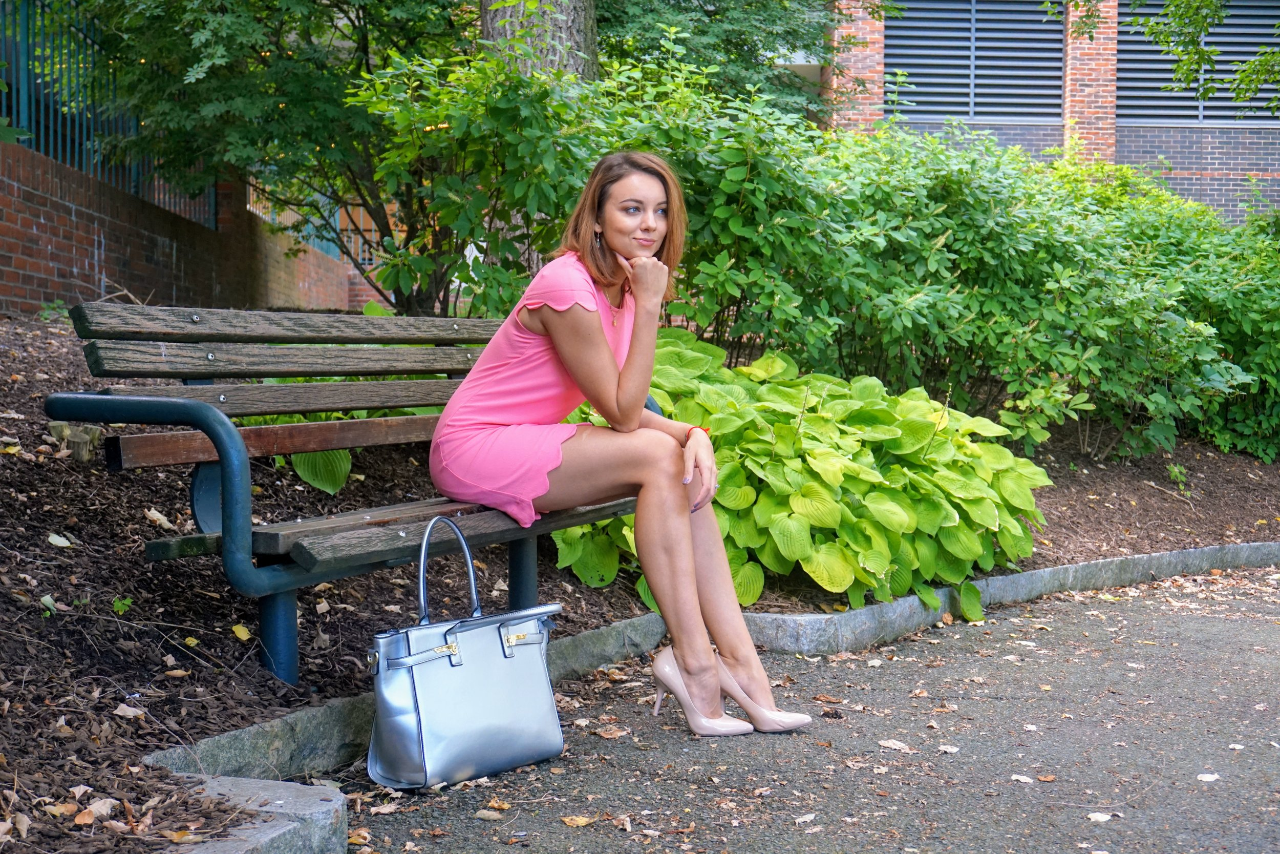 A fashion blogger sitting on a bench in Boston, wearing a romantic look: pink dress, nude heels, siler bag.