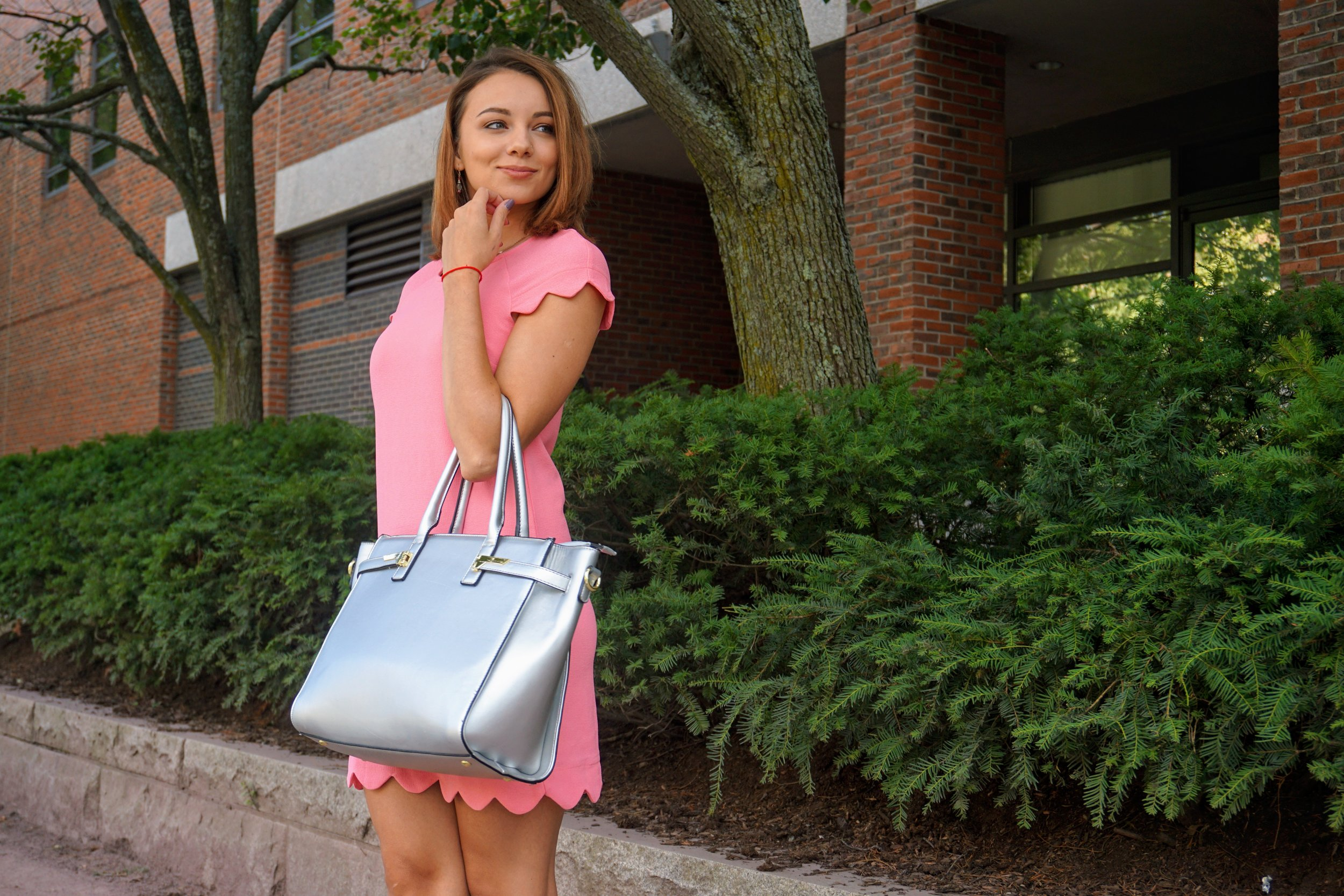 A blogger standing near the tree, wearing a pink dress, silver bag, and nude heels.